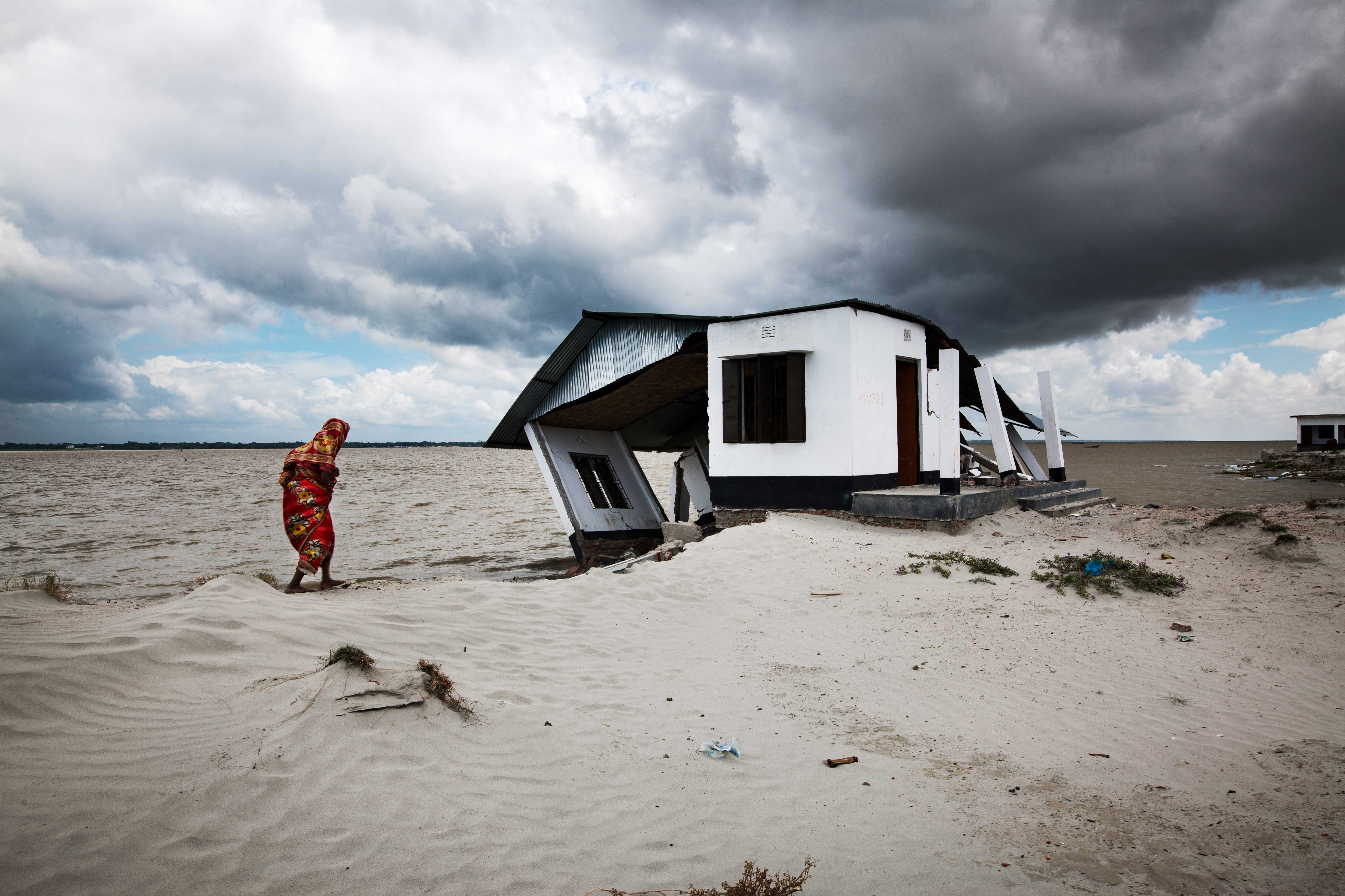 A woman walks to her eroded shelter home near the Meghna river in Bangladesh.