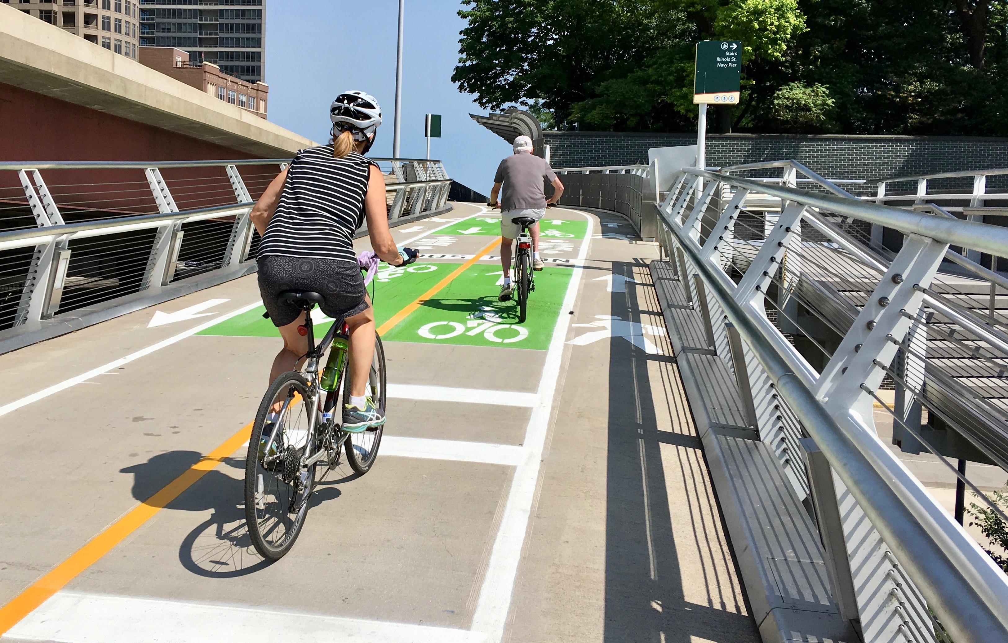 Two bikers on a concrete bike path.