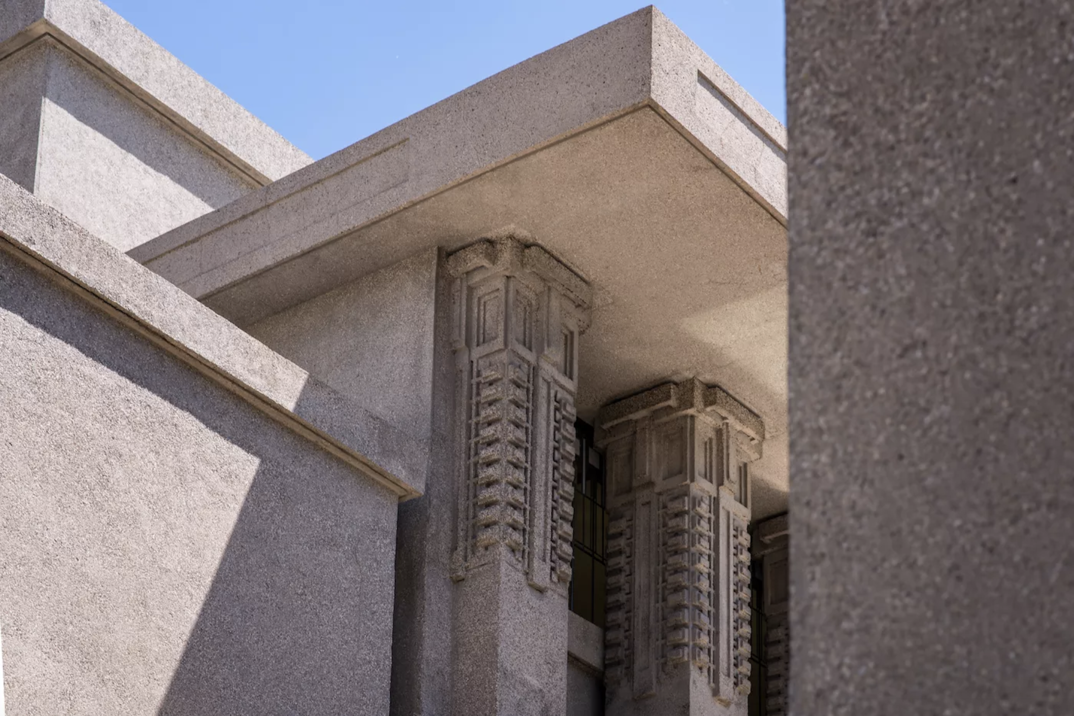A windowless concrete building with slab sides and minimal ornaments on its columns.
