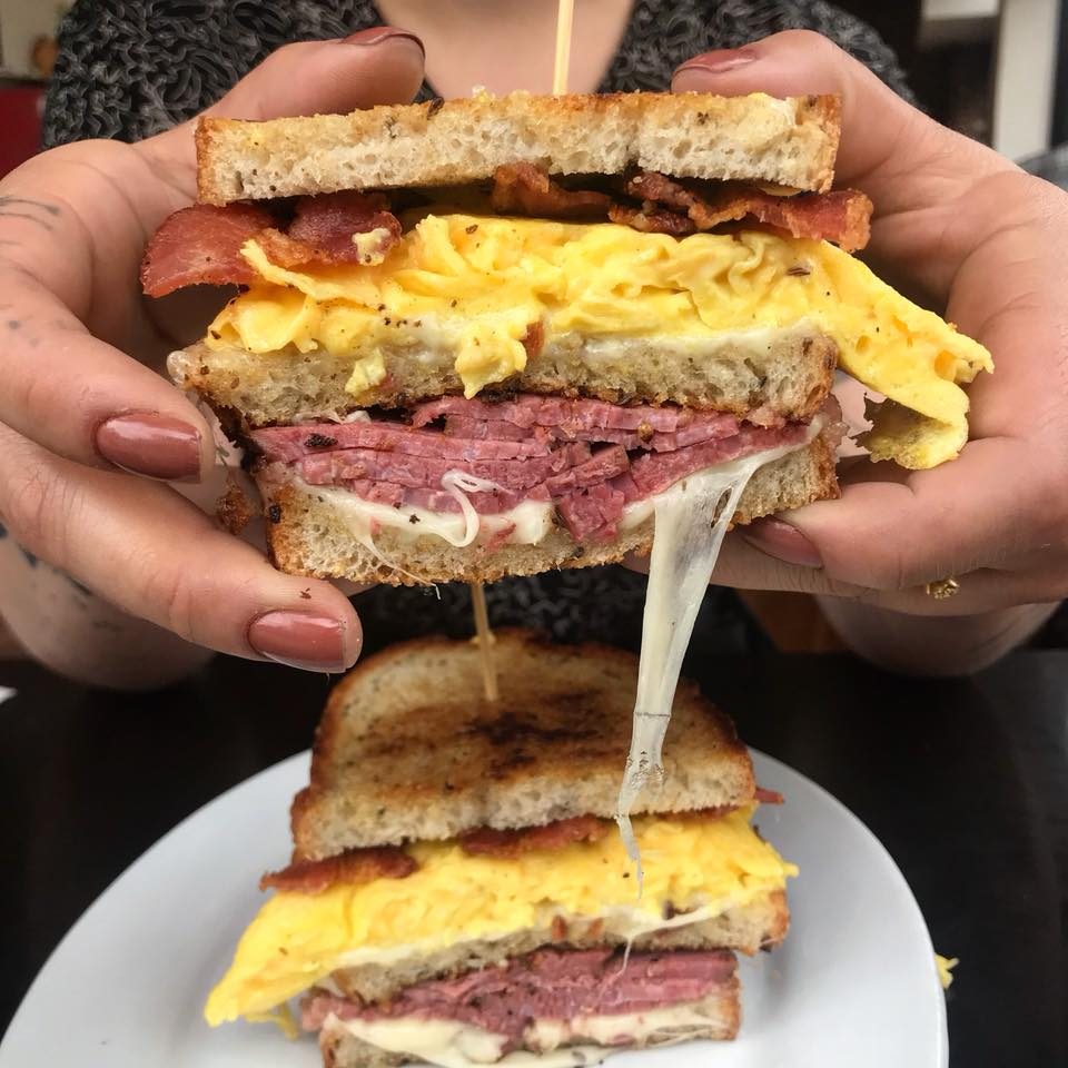 A picture of a person holding a massive breakfast sandwich at Kenny & Zuke's