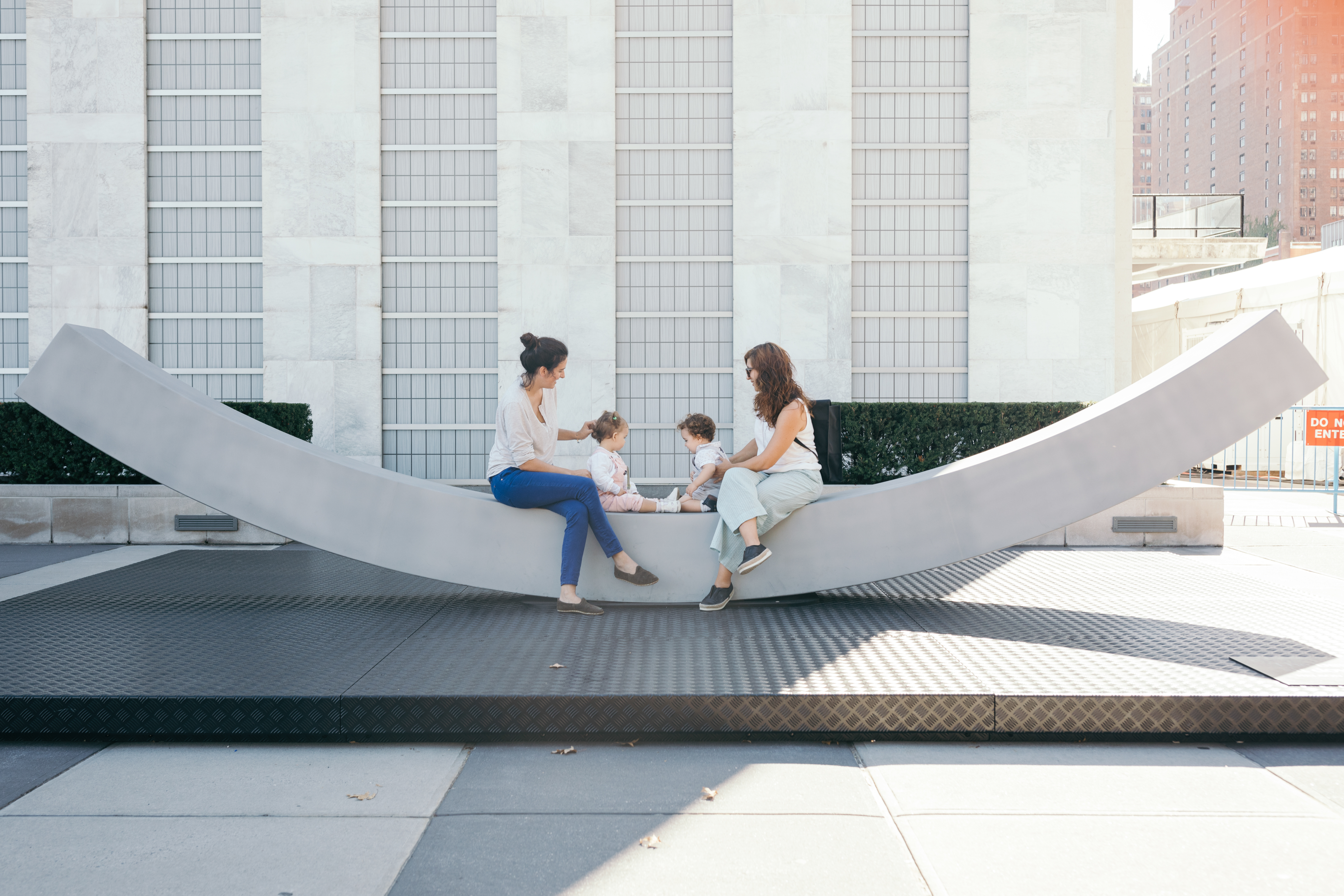 Two moms and babies sitting on arched bench.
