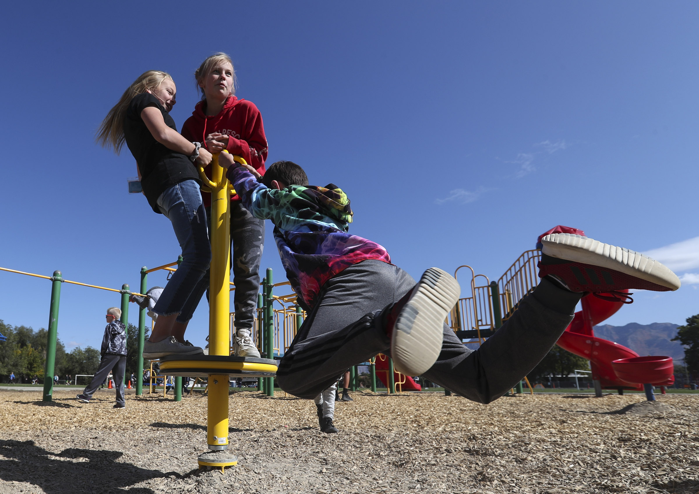 Sixth graders work together to twirl on a new piece of playground equipment during lunch recess at Liberty Elementary School in Murray on Thursday, Oct. 10, 2019.