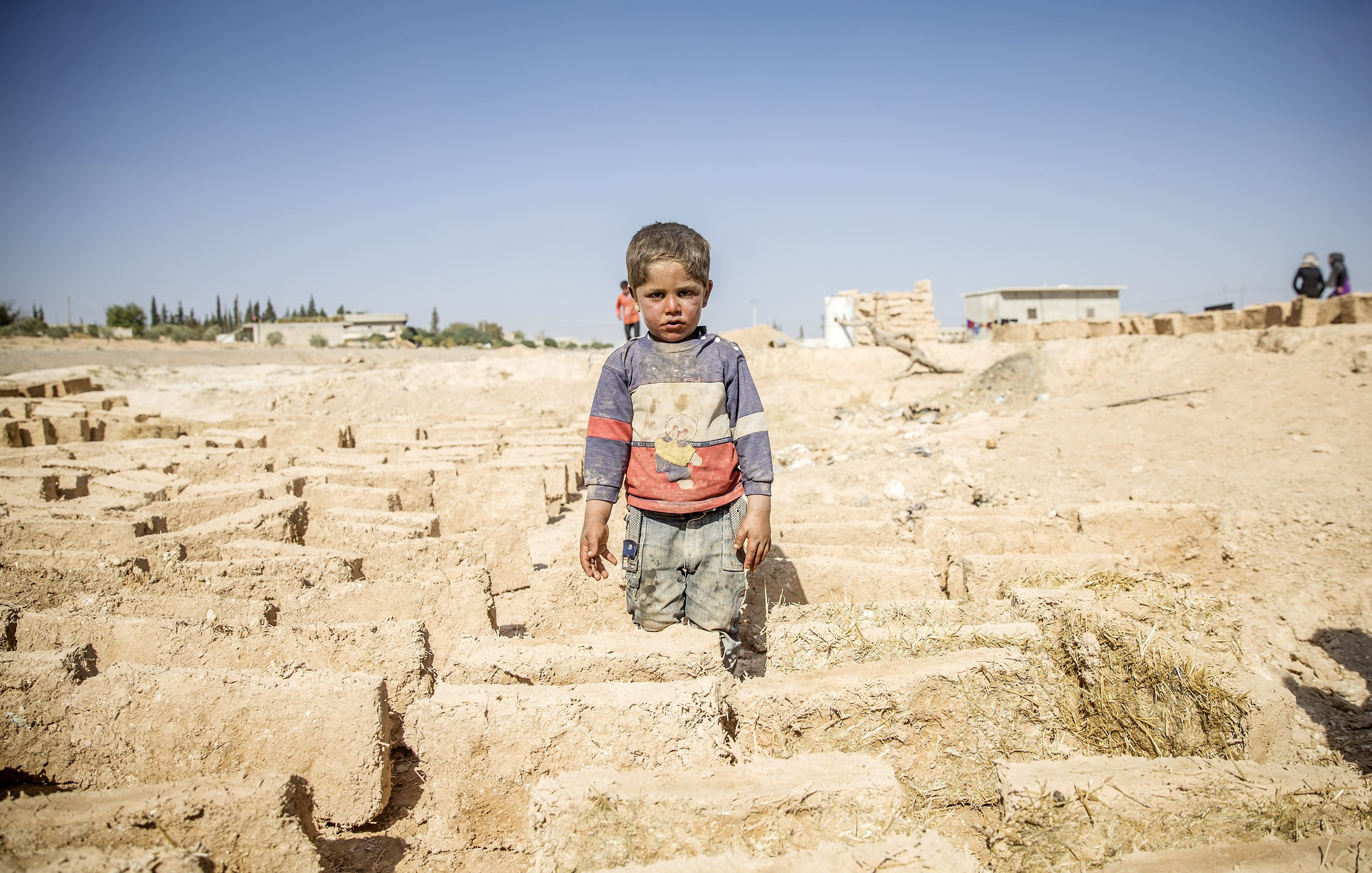 A small Syrian boy standing in a desert-like place.