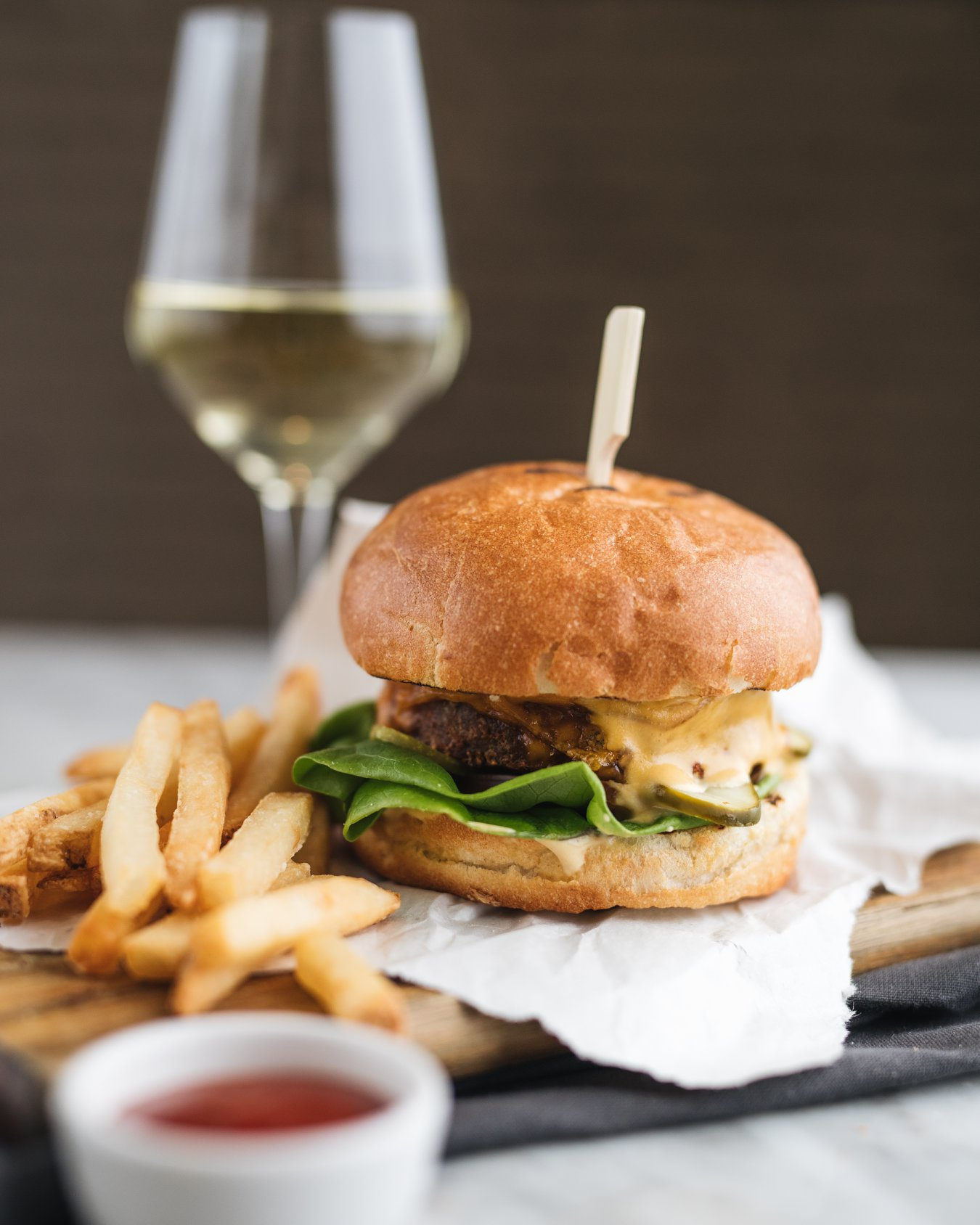 A burger with fries on a wooden platter in front of a wine glass.