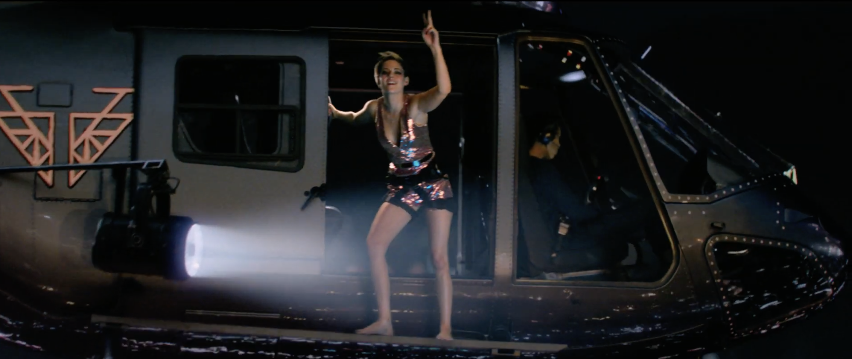 Kristen Stewart looking fierce in a sparkly pink dress, while grasping onto a helicopter