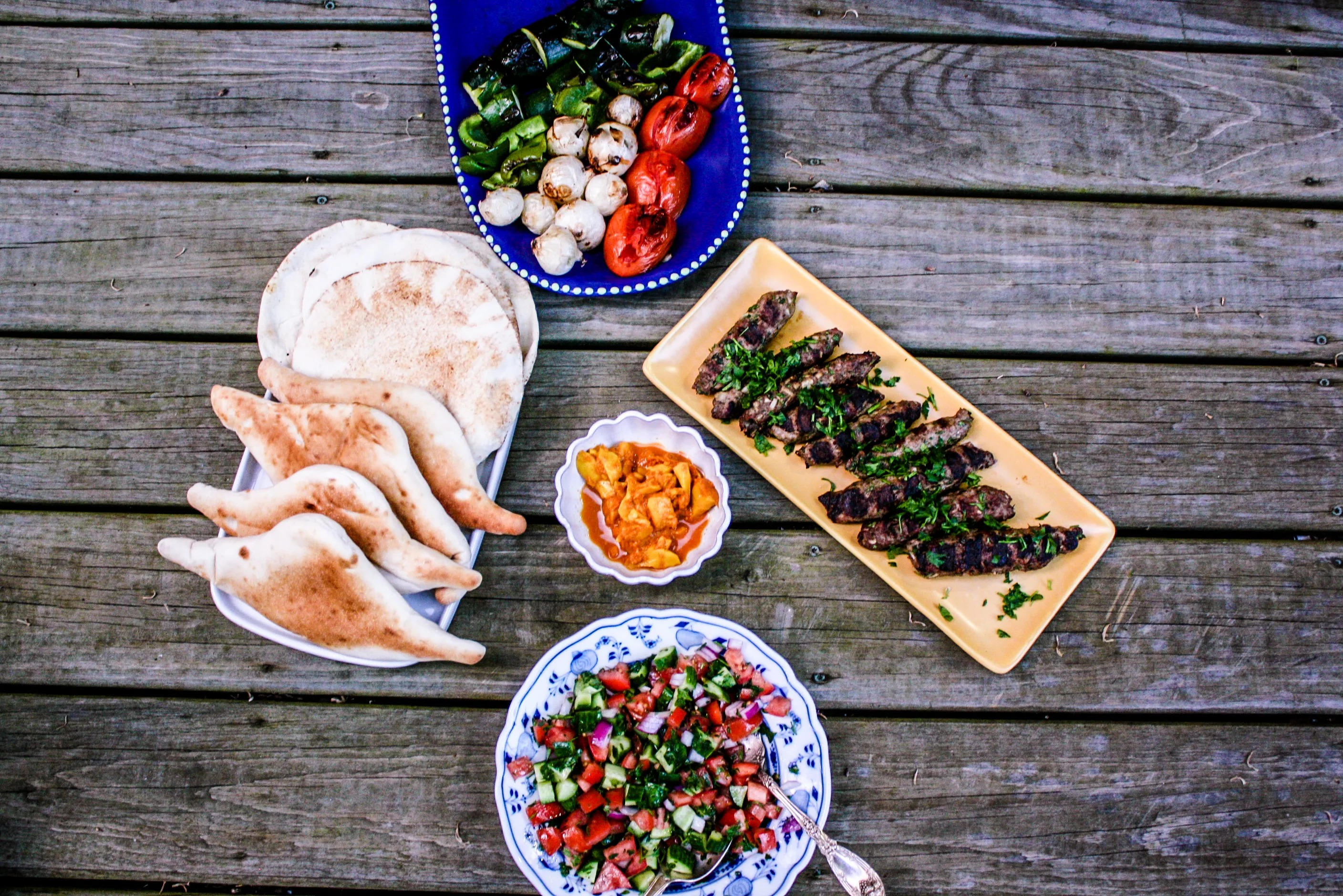 Trays of vegetables and pita sit on a wooden table