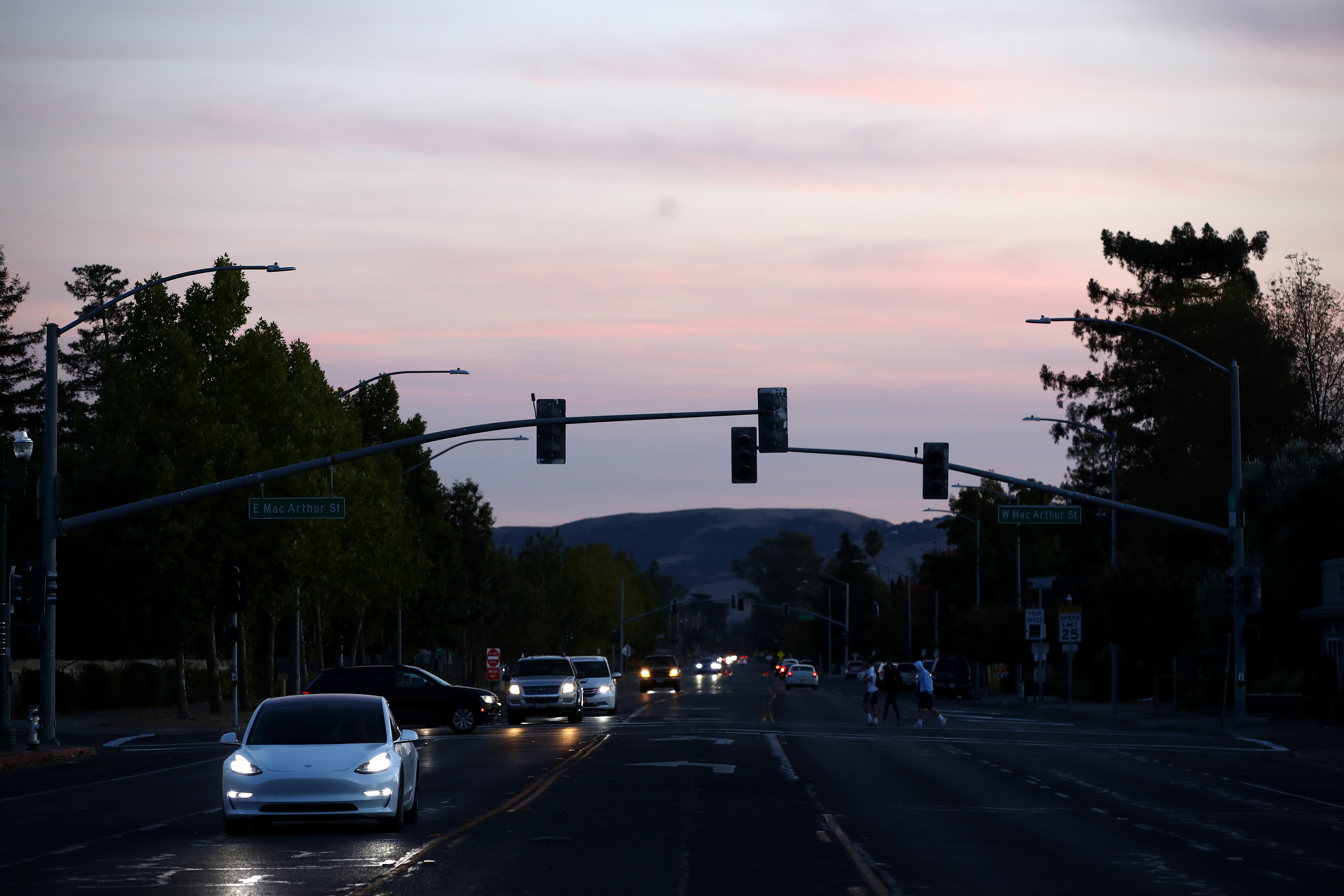 An intersection with darkened traffic lights and cars with their headlights on.