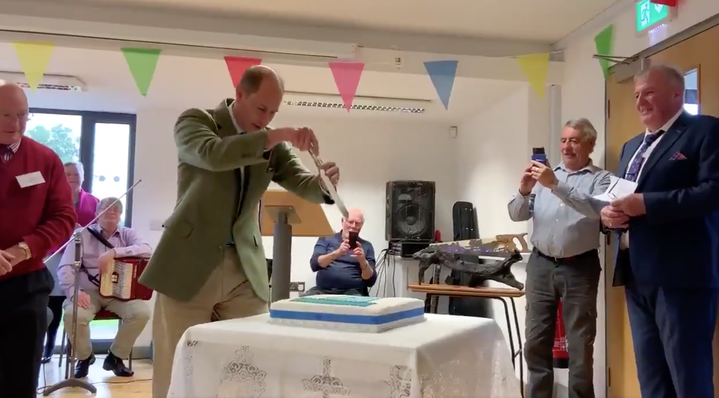 A balding white man holding a knife high above a sheet cake