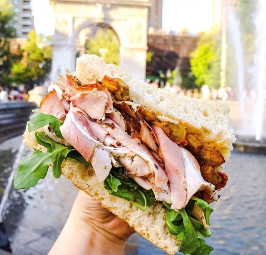 A sandwich from Italy protrudes with sliced meat and focaccia.