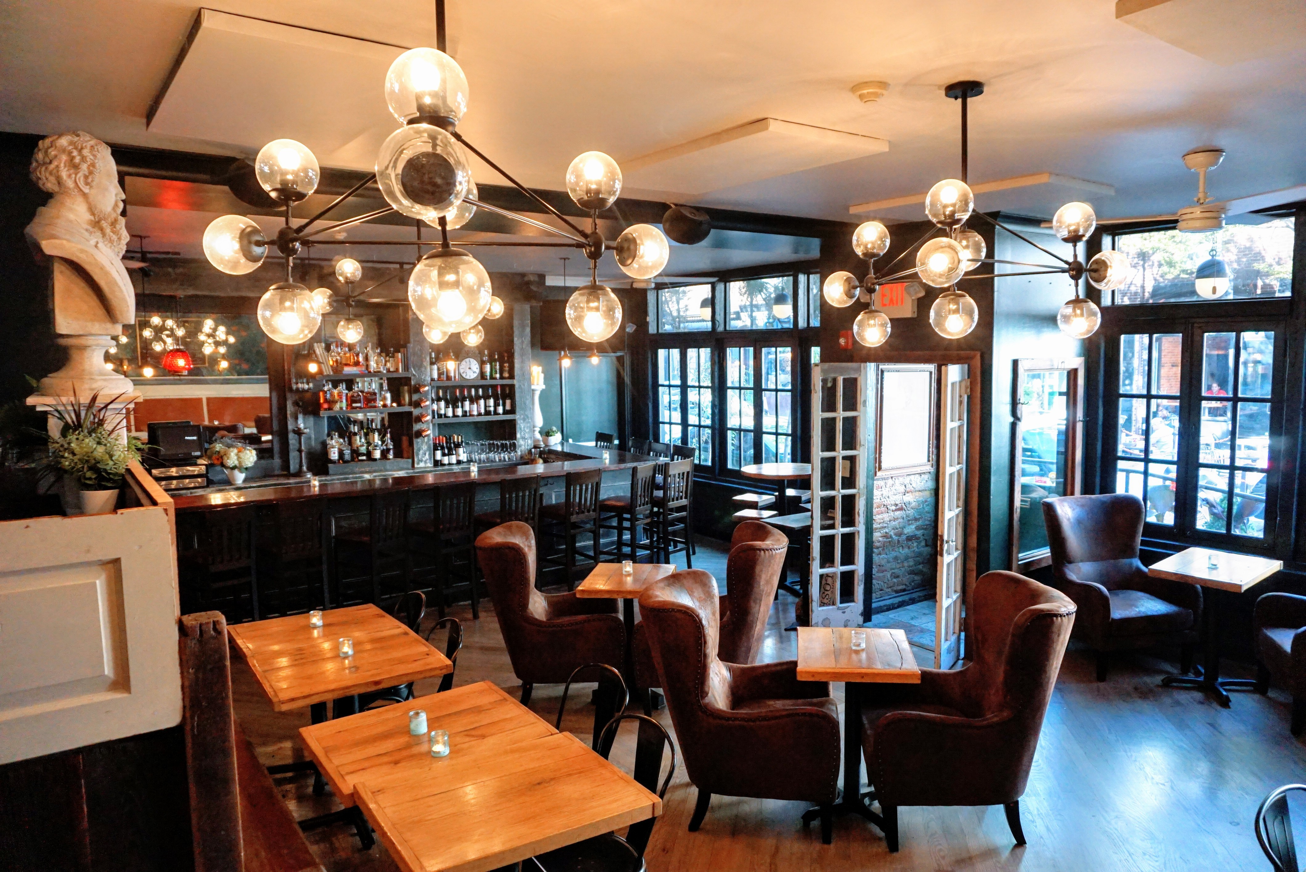 a restaurant with plush seats, globe lights, and a bust