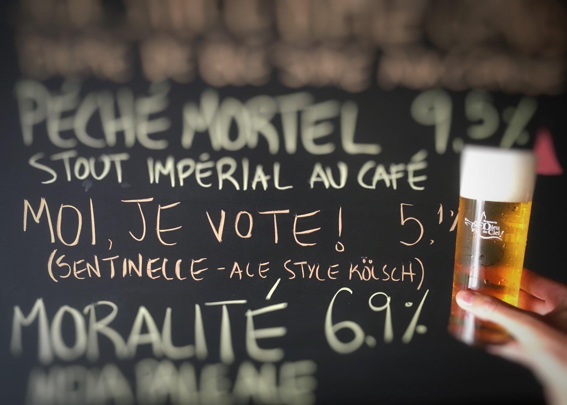 "A chalkboard reading ""Moi Je Vote"" with a beer held alongside it."