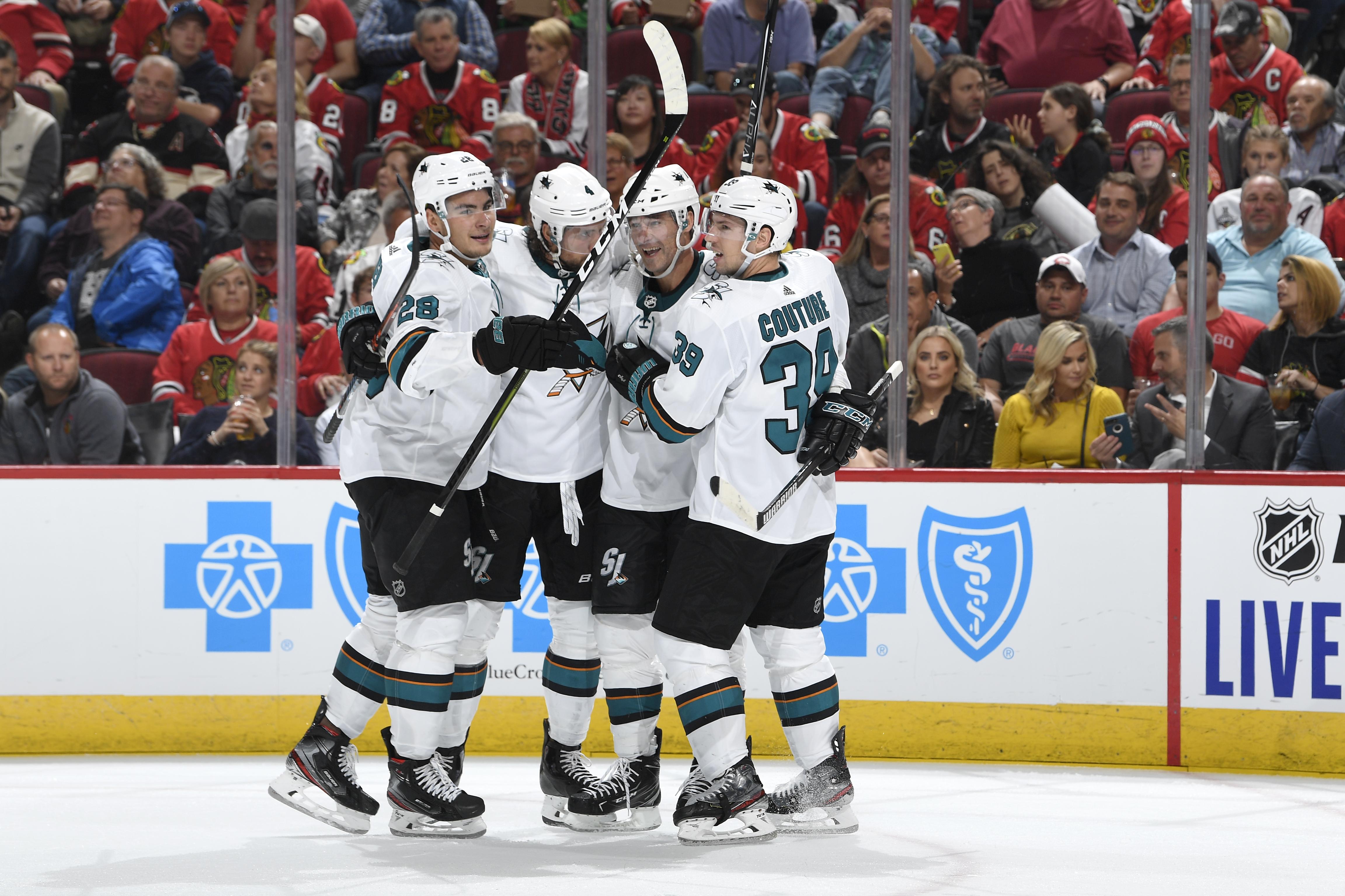 Timo Meier #28, Brenden Dillon #4, Patrick Marleau #12 and Logan Couture #39 of the San Jose Sharks celebrate after scoring against the Chicago Blackhawks in the second period at the United Center on October 10, 2019 in Chicago, Illinois.