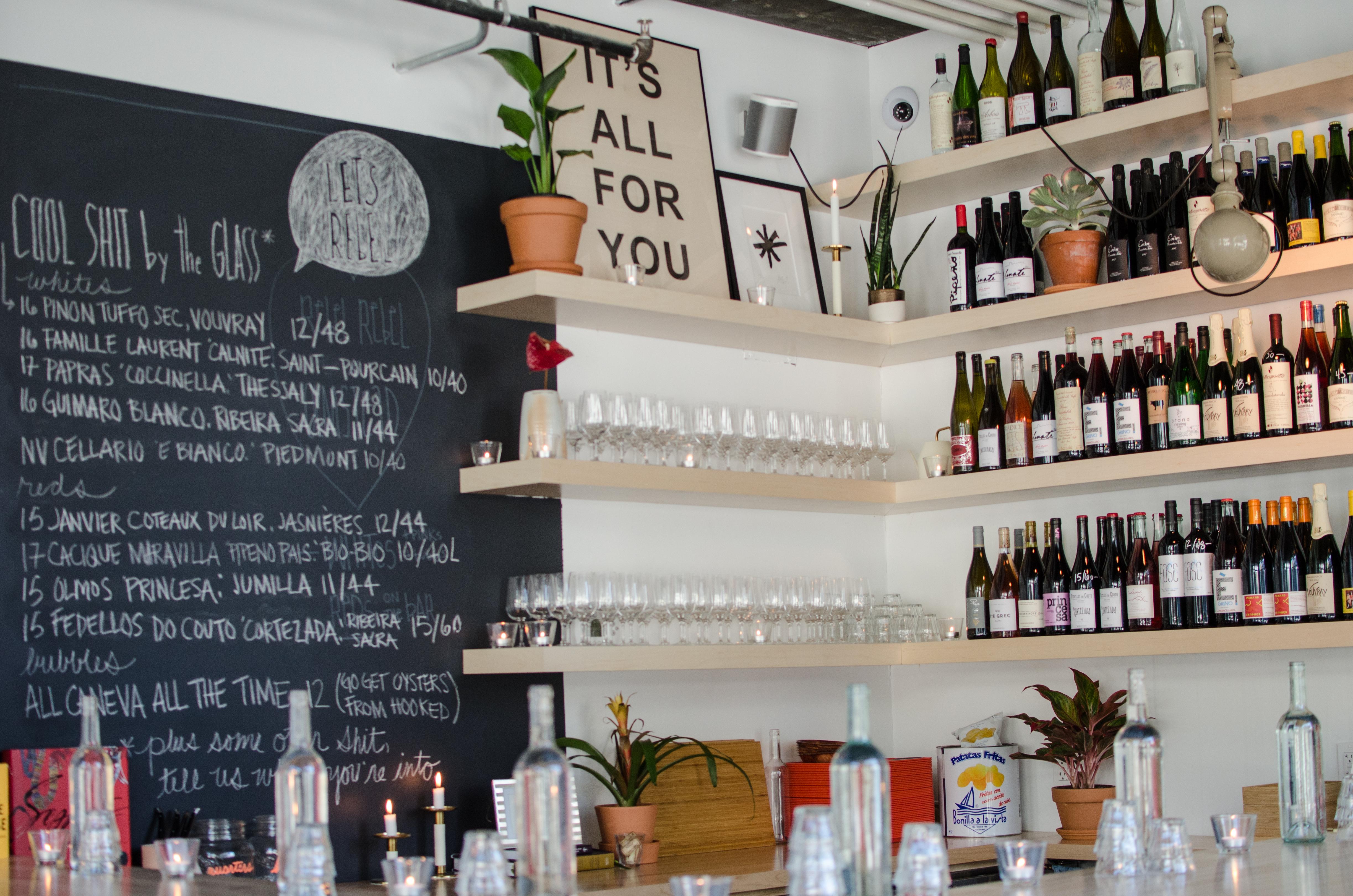 Shelves of wine bottles and a chalkboard menu inside a wine bar