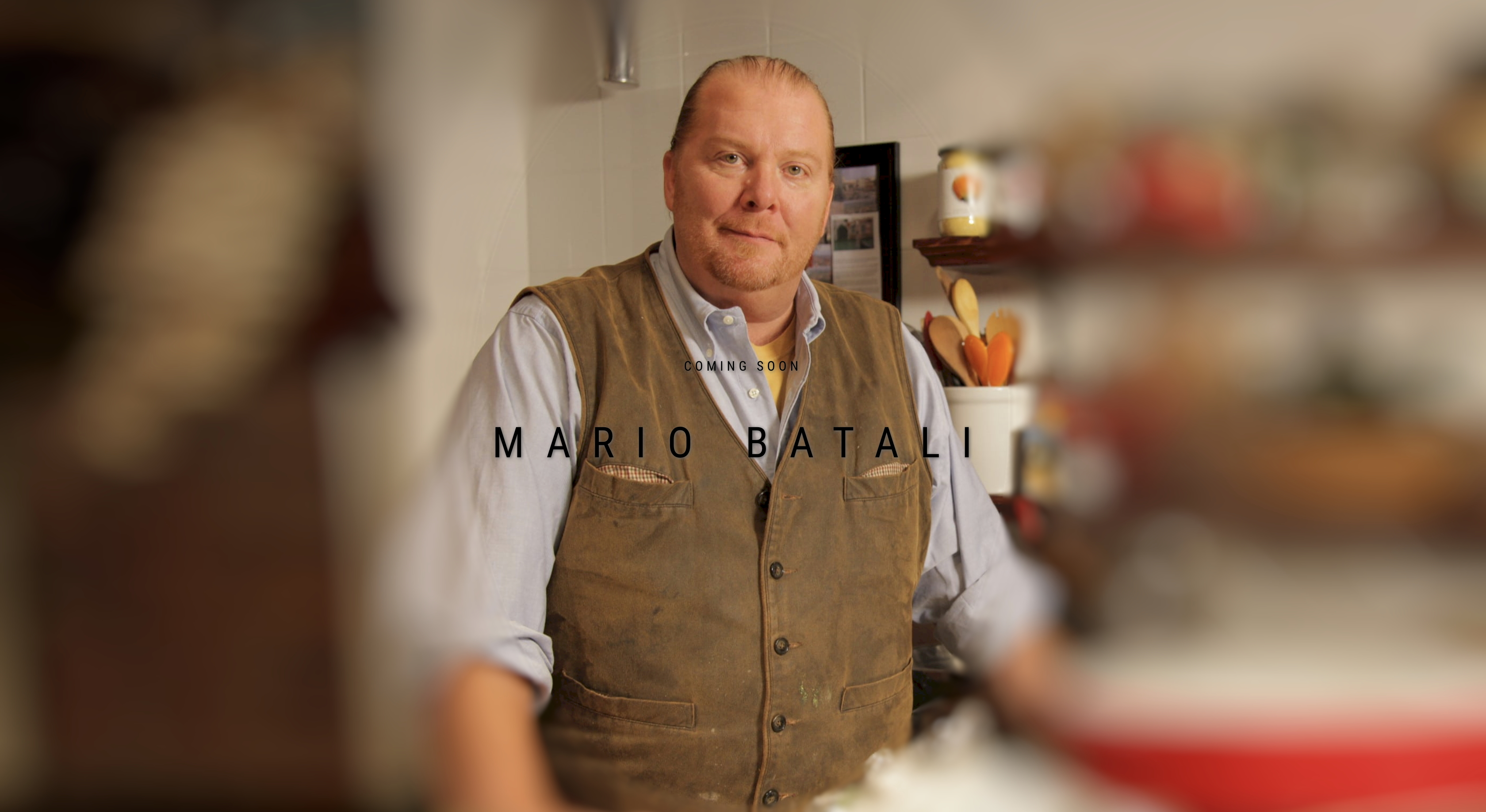 "A man, Mario Batali, stands in a kitchen. The photo is blurred on either side of the standing figure and words across the screen read ""coming soon, Mario Batali"""