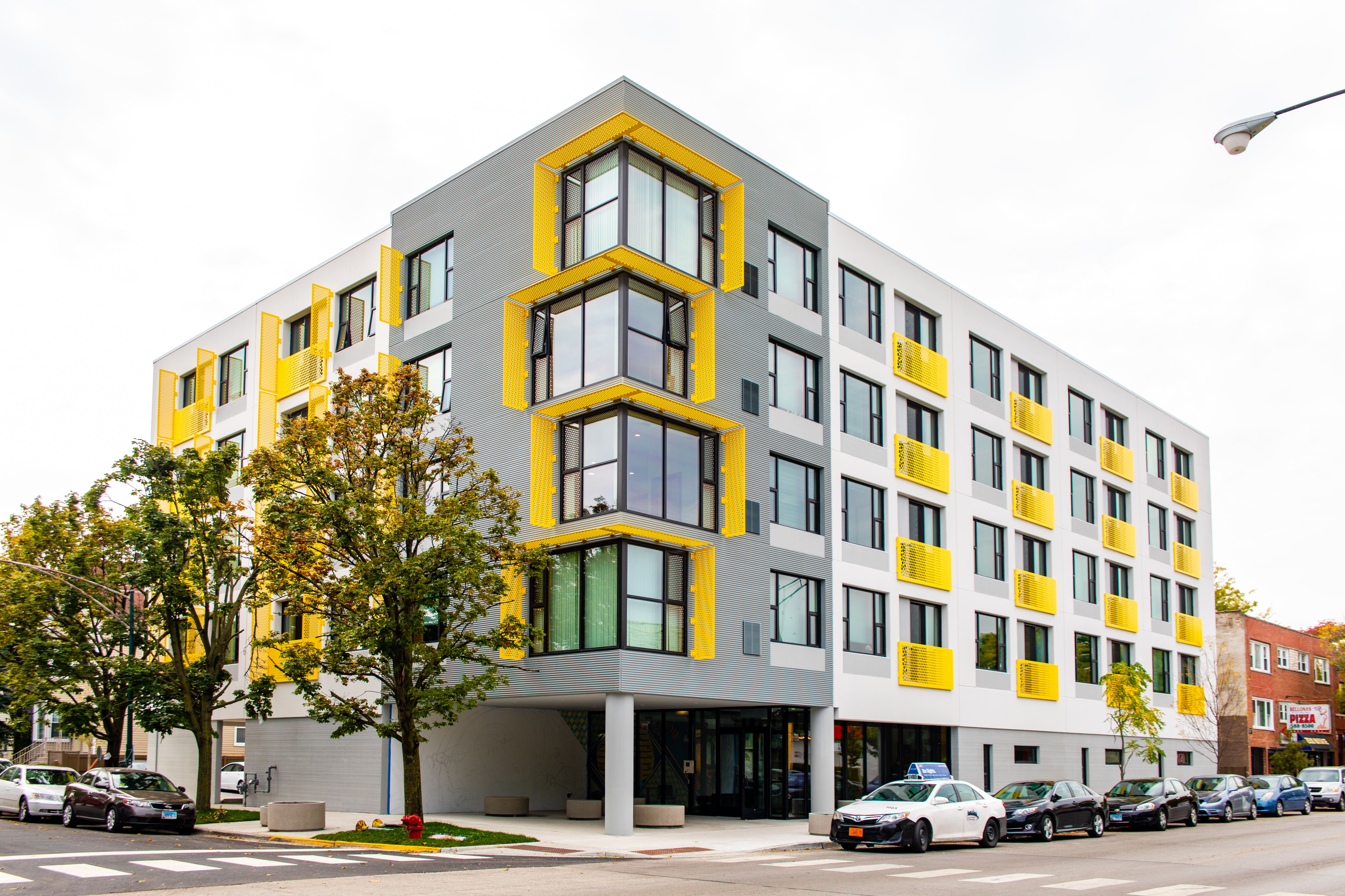 A five-story apartment building with a white and gray facade and yellow accents around the windows and in front of the balconies.