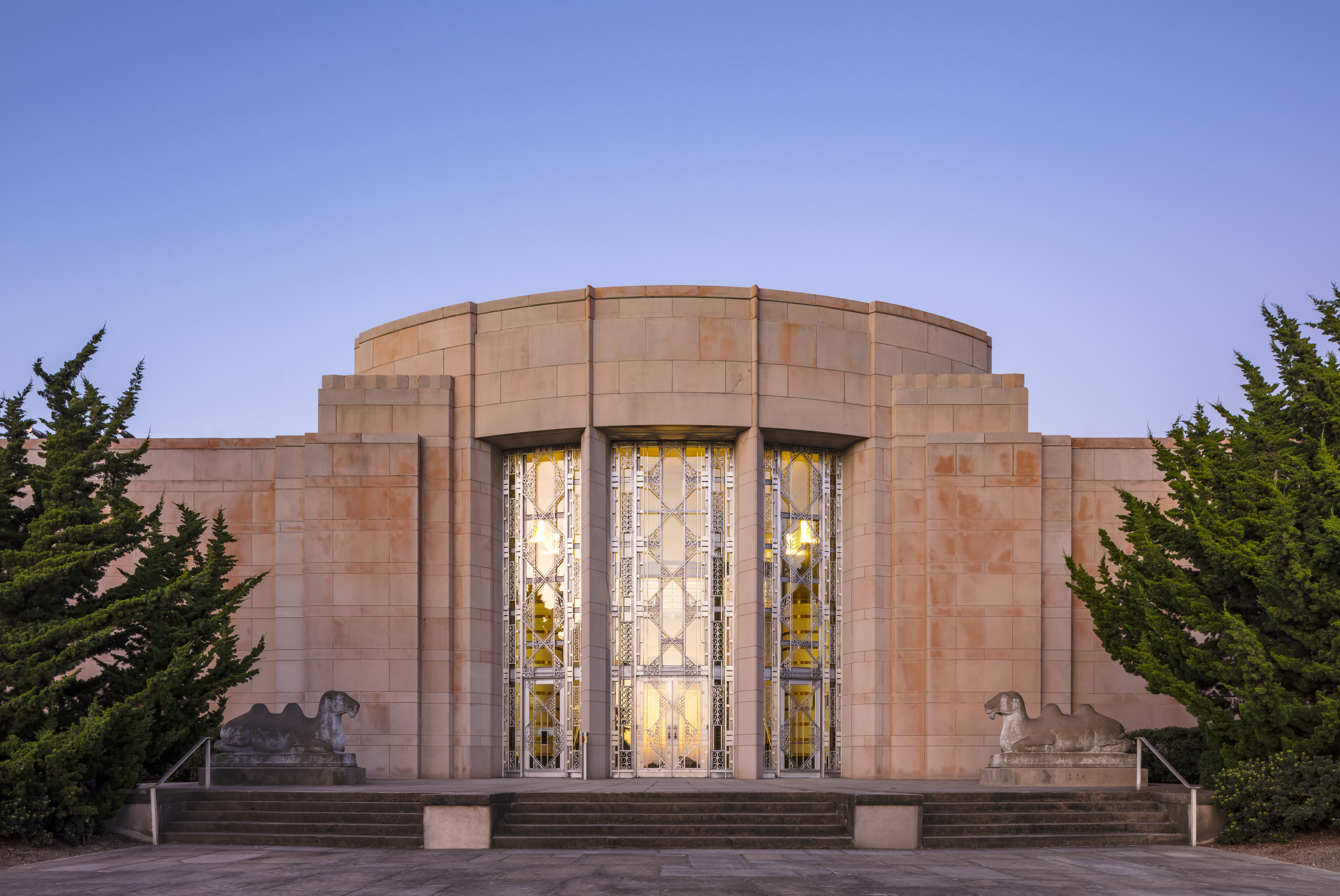 On a clear day at dusk, an Art Deco building with a large central bay with three vertical, ornate window. There's a wide staircase up to the front with camels on either side. The facade is clean and tidy, and light shines through the windows' amber glass.