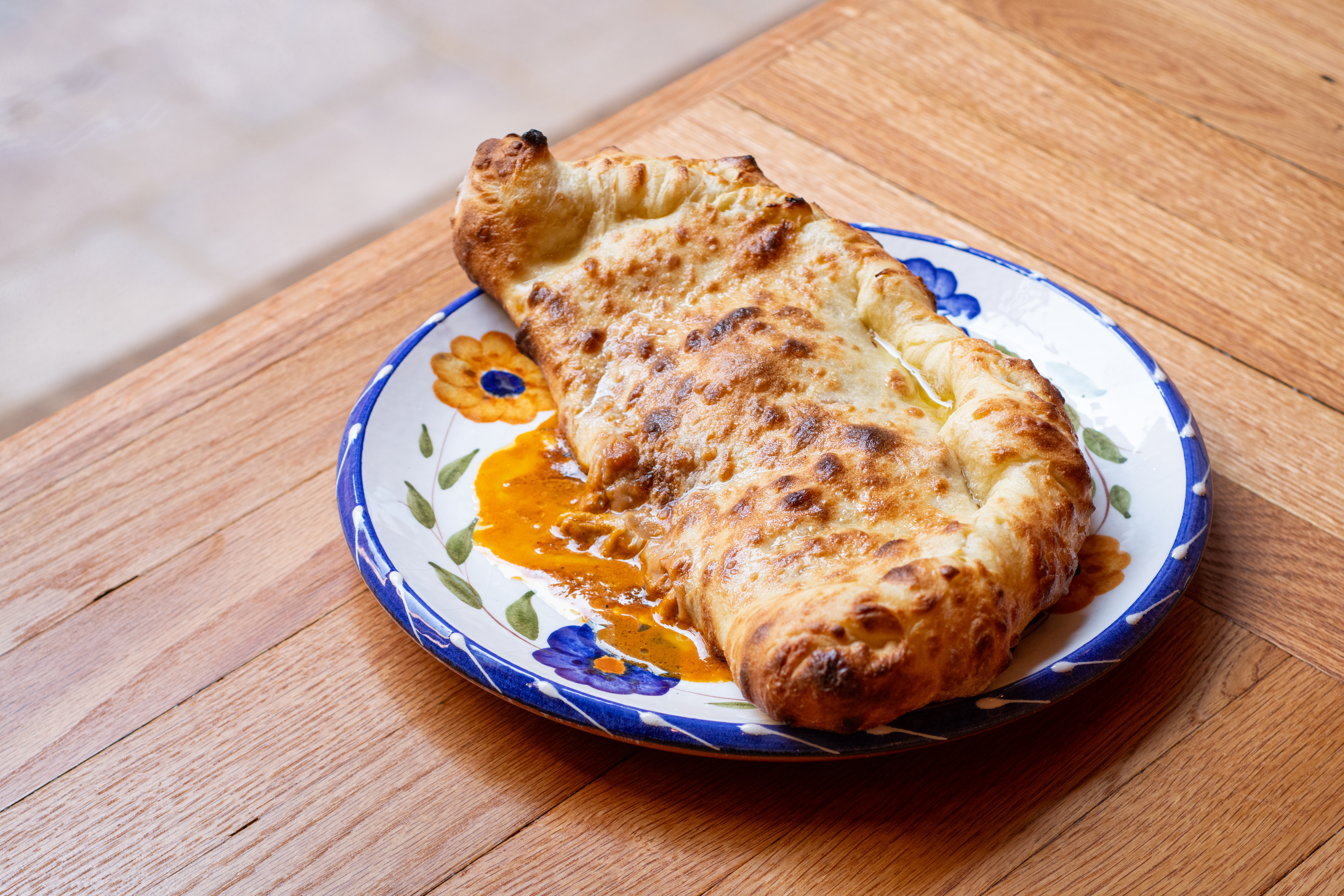 A baked and folded naan bread pocket on a blue and white plate stuffed with orange butter chicken sauce.