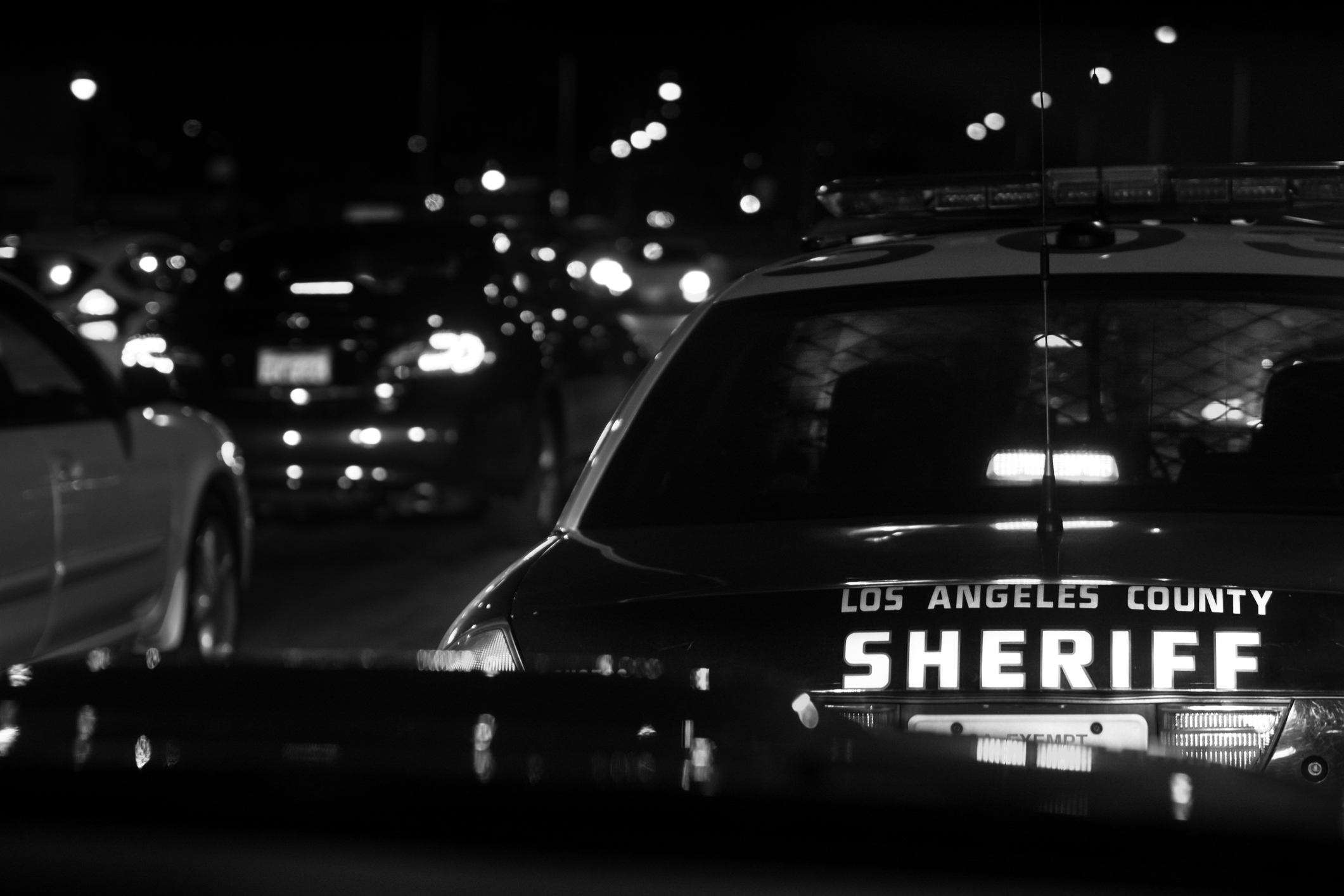 "A squad car with the words ""Los Angeles County Sheriff"" on the back driving through traffic."