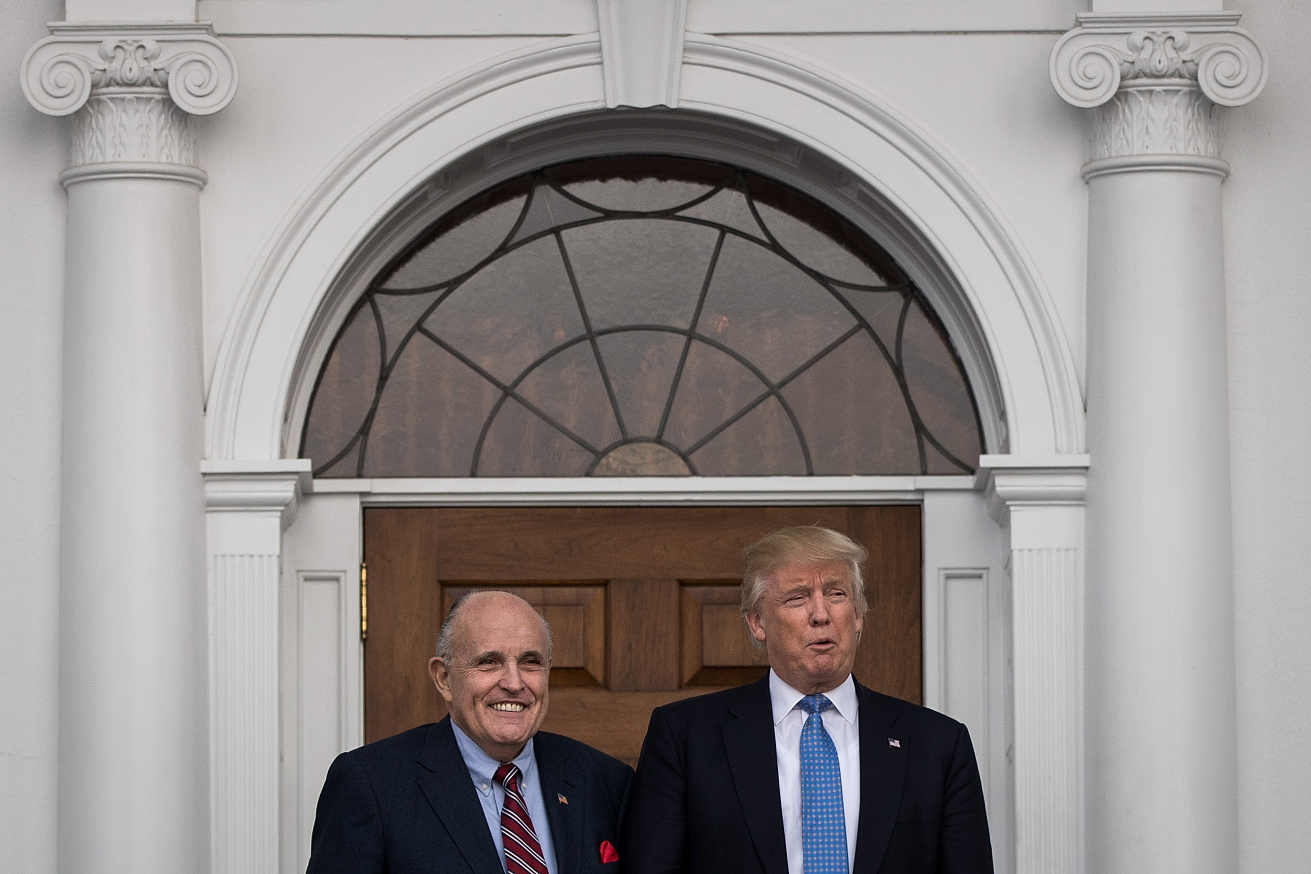 Giuliani and Trump stand between two white columns, smiling.