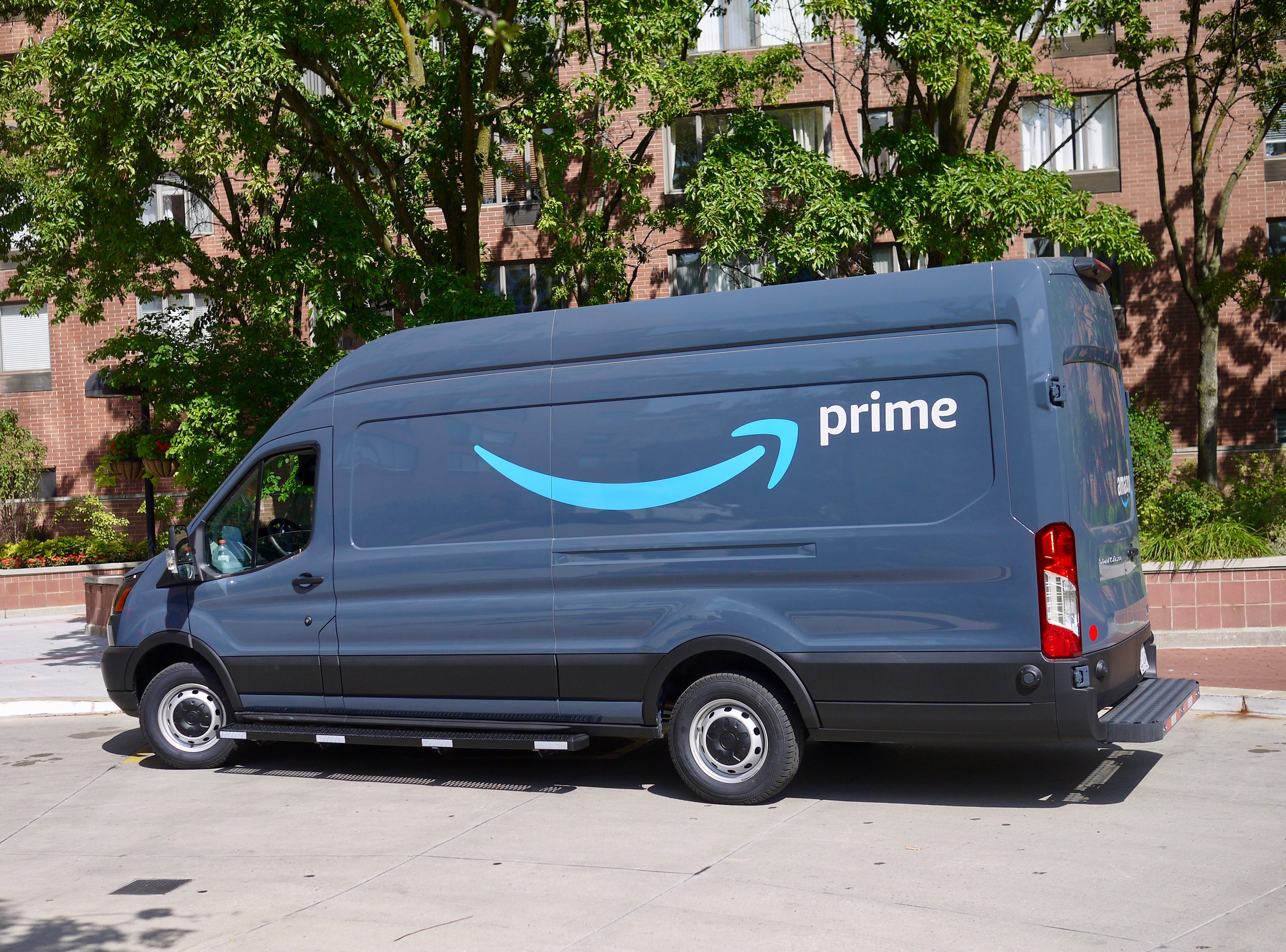 """An Amazon delivery van with the smile logo and the word """"prime"""" painted on the side."""