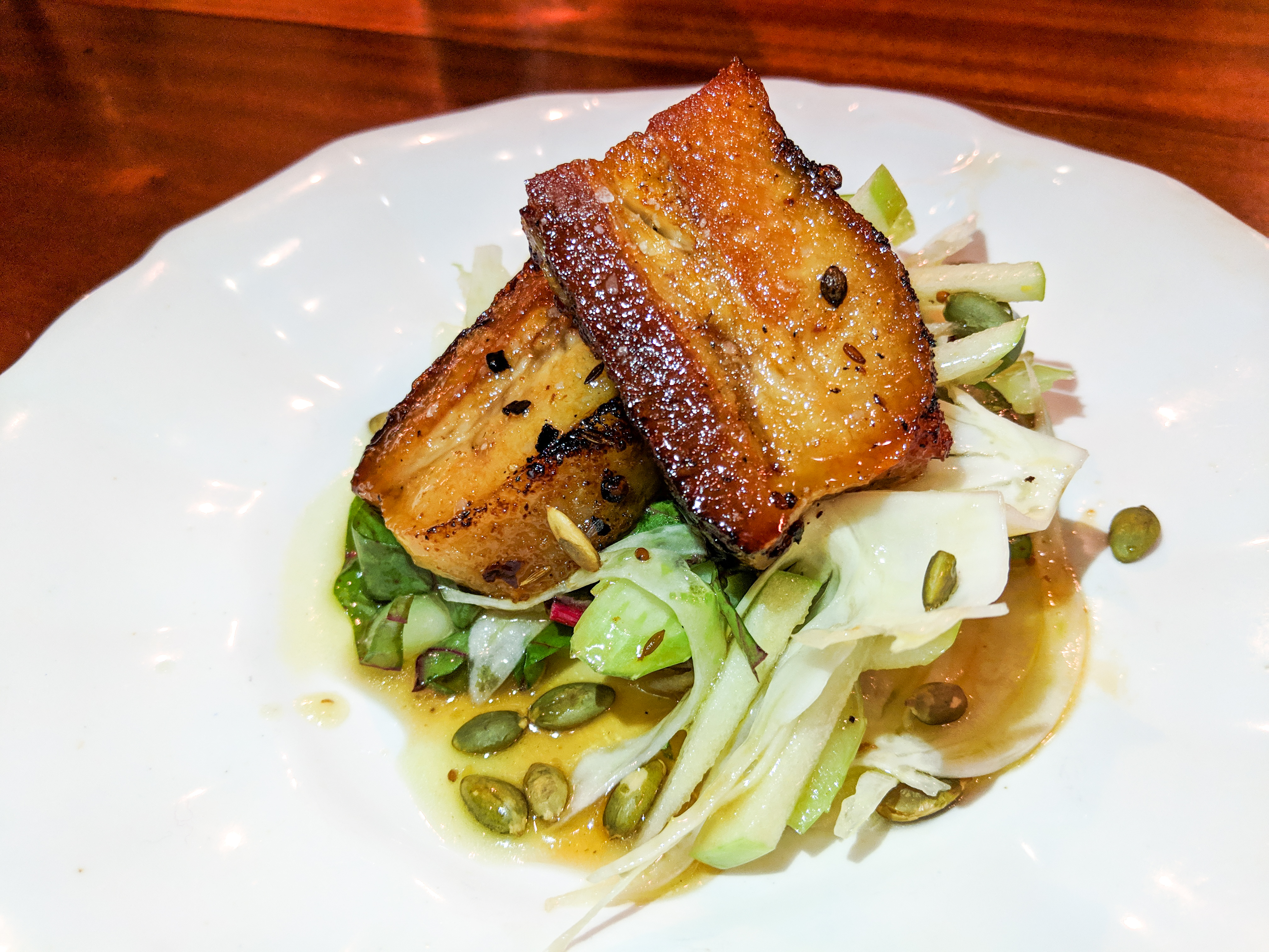 Two slabs of pork belly sit on a white plate with greens and other accoutrements. The plate is on a glossy wood bar.