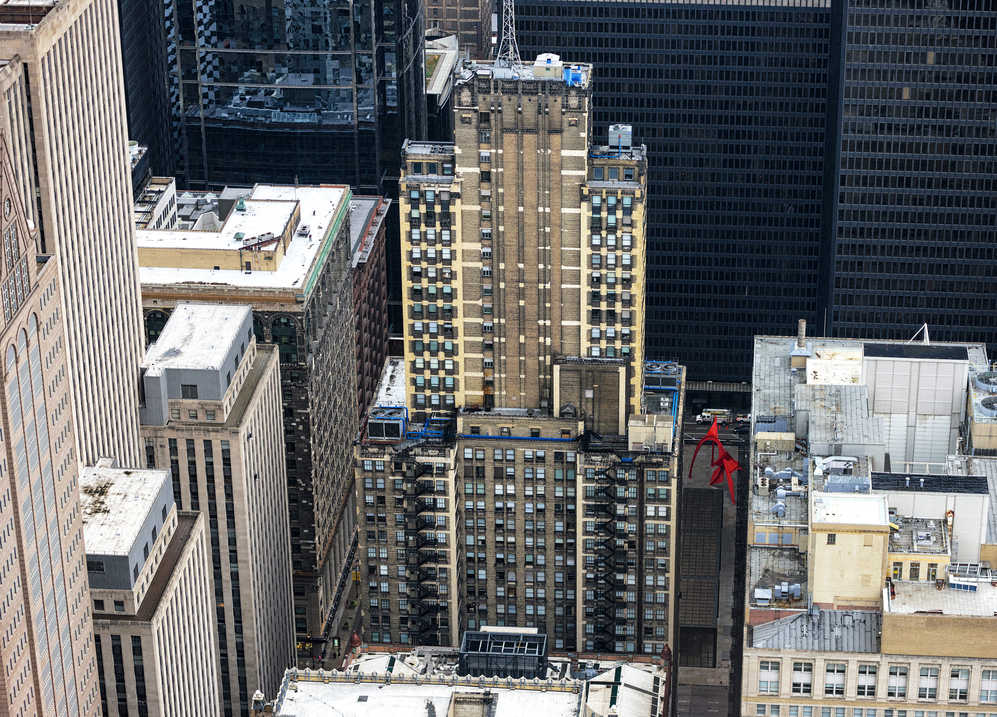 An aerial image of an 41-story office building with a mismatched brick exterior of beige and brown bricks. The building is surrounded by other tall high-rise buildings.