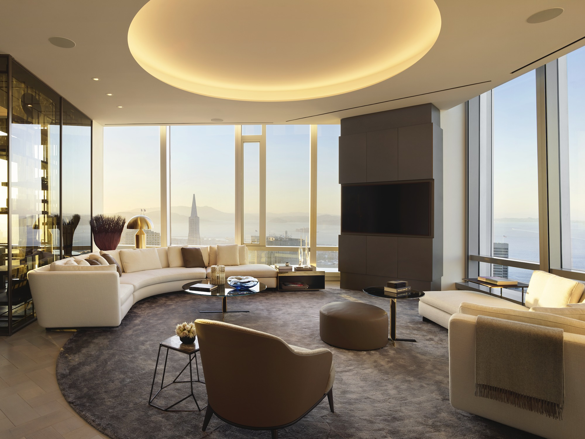 A living room with a circular indentation in the ceiling with recessed lighting inside, widows galore with views of the city and the fog, and half-circle couch and seating.