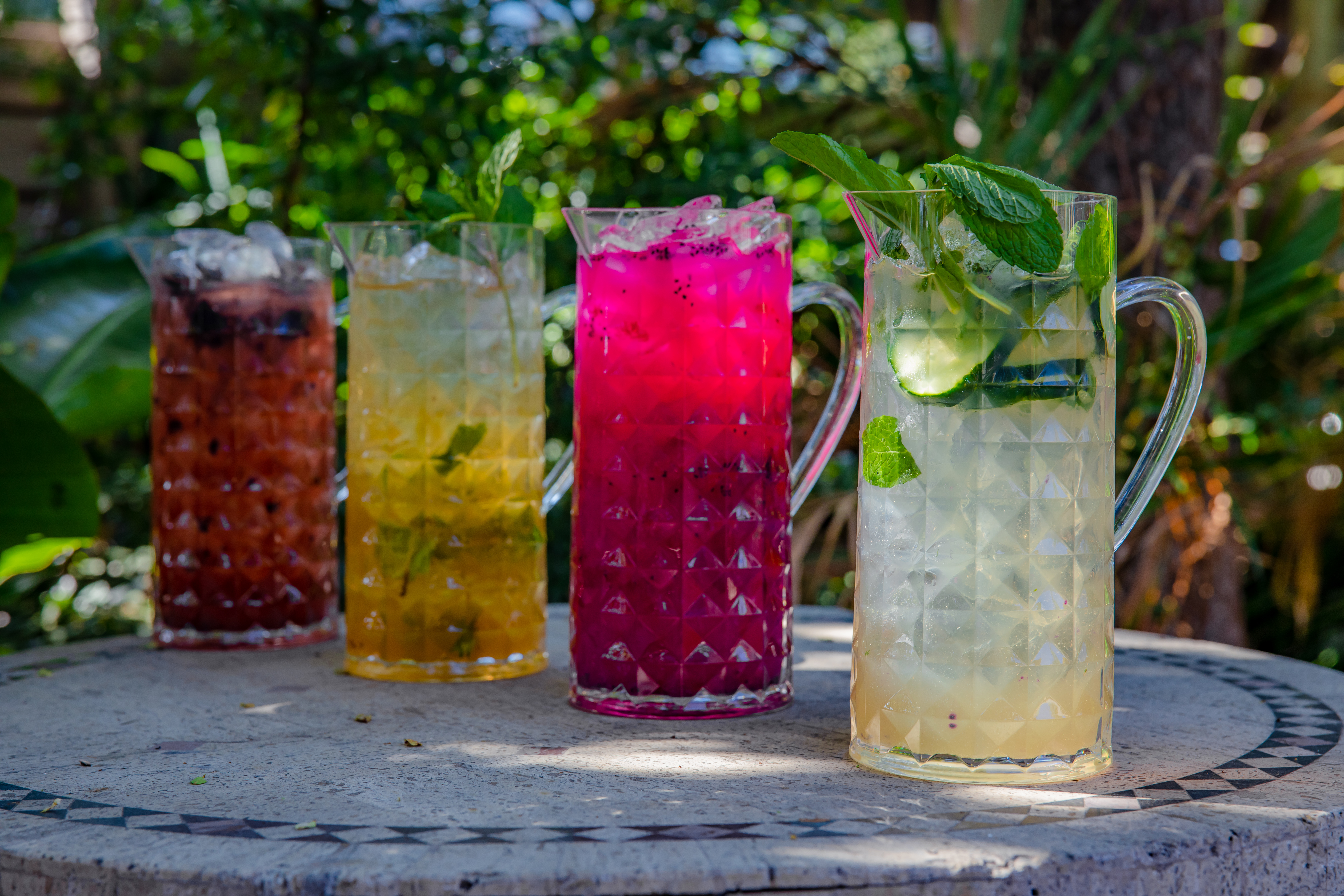 row of four pitchers with drinks