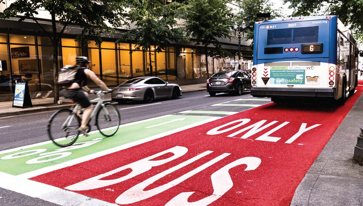 A bright red bus-only lane runs down a city street with a blue bus in the lane and a person riding a bike in the green bike lane to the left of the bus.