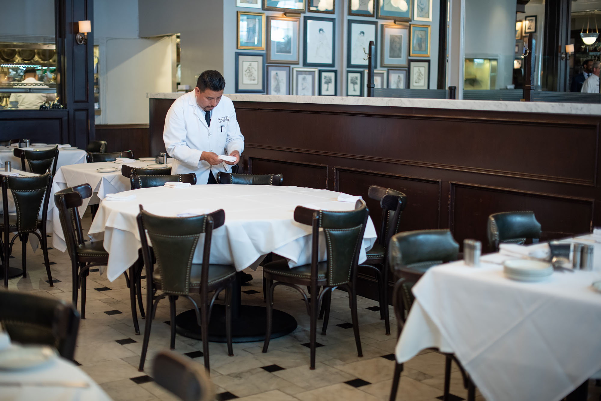A server sets down napkins at a fine dining restaurant in prep for service.