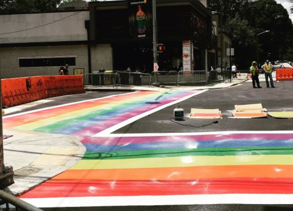 Work progressing on painting the rainbow crosswalk.