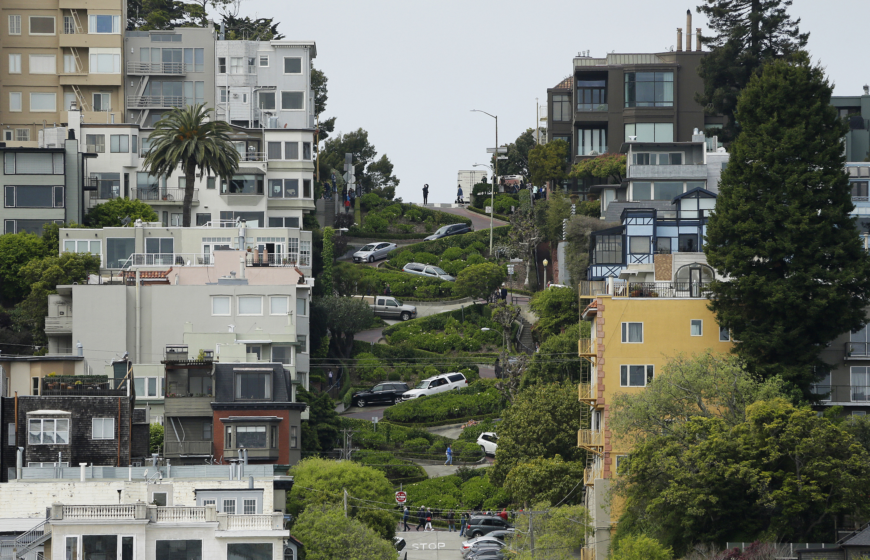 Cars wind their way down Lombard Street in San Francisco, a crooked street flanked by homes and apartment buildings.