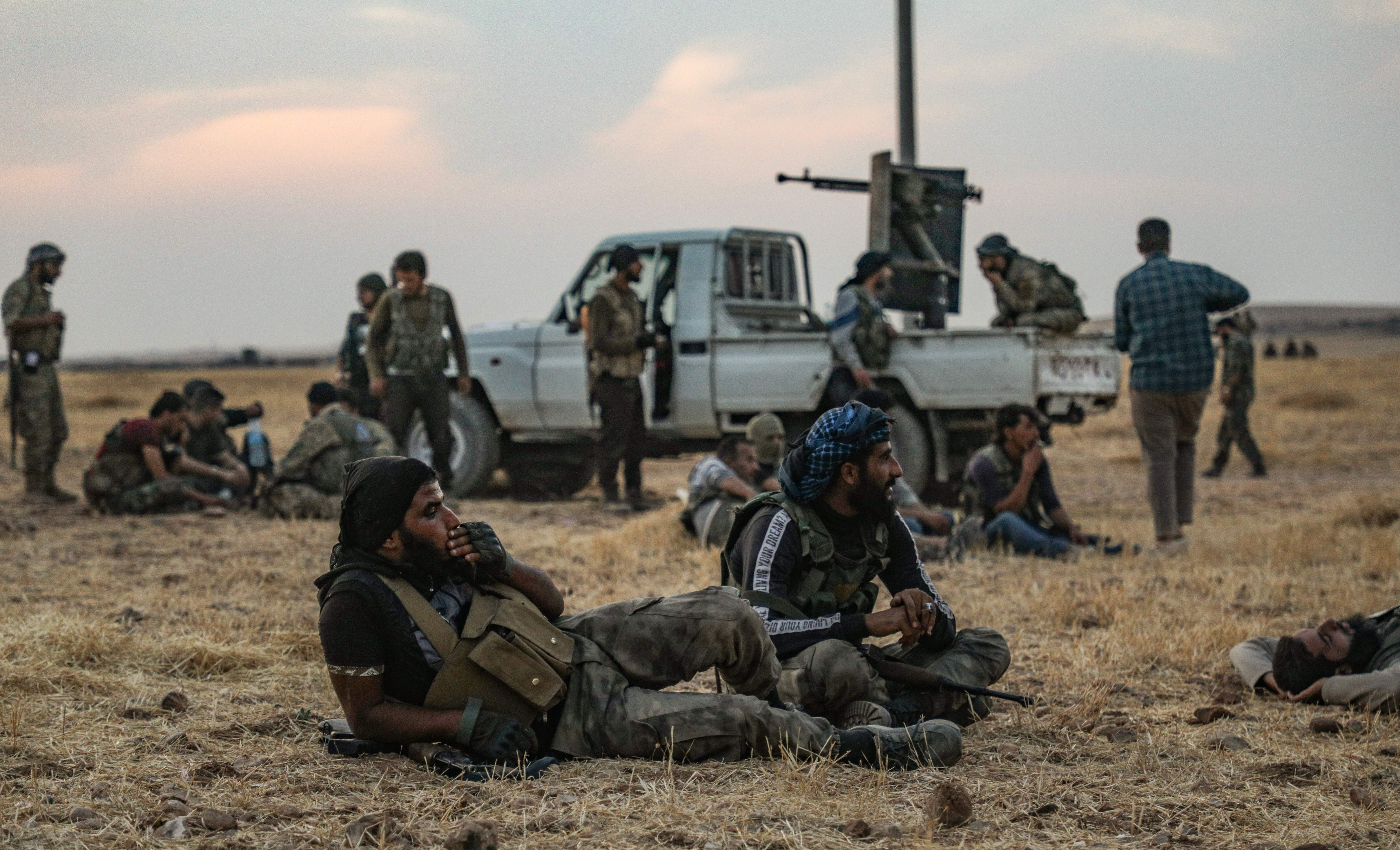 Turkish-backed Syrian fighters rest in front of a truck.