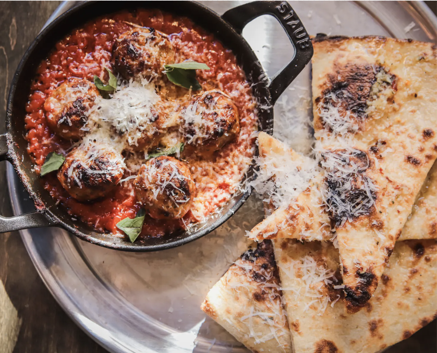 A cast-iron pot holds meatballs and tomato sauce beside grilled triangles of flatbread.