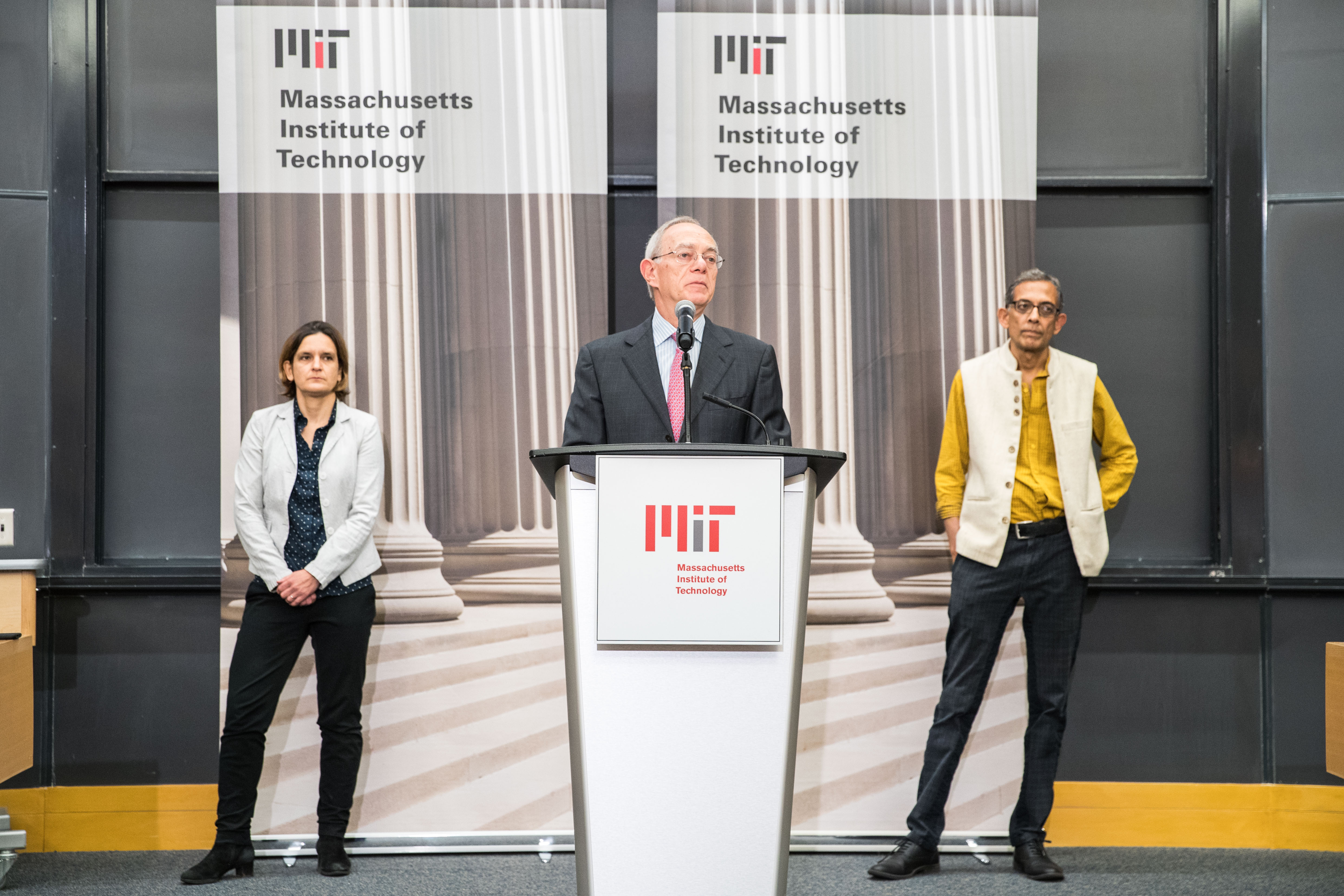 MIT's president stands onstage at a podium introducing the winners of the Nobel Prize in Economics standing to his left and right.