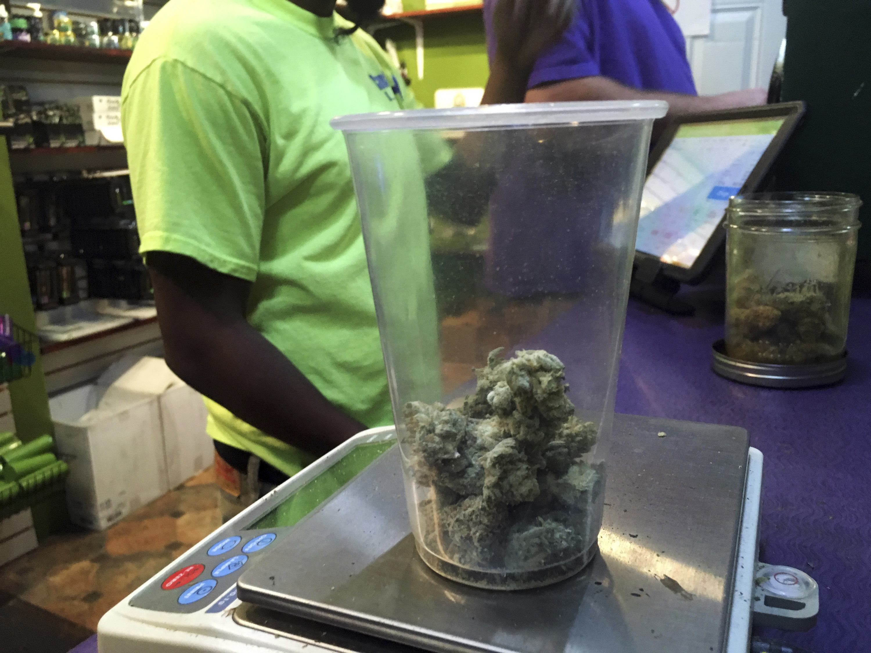 A clear cup filled with marijuana is weighed on scale at a cannabis dispensary.
