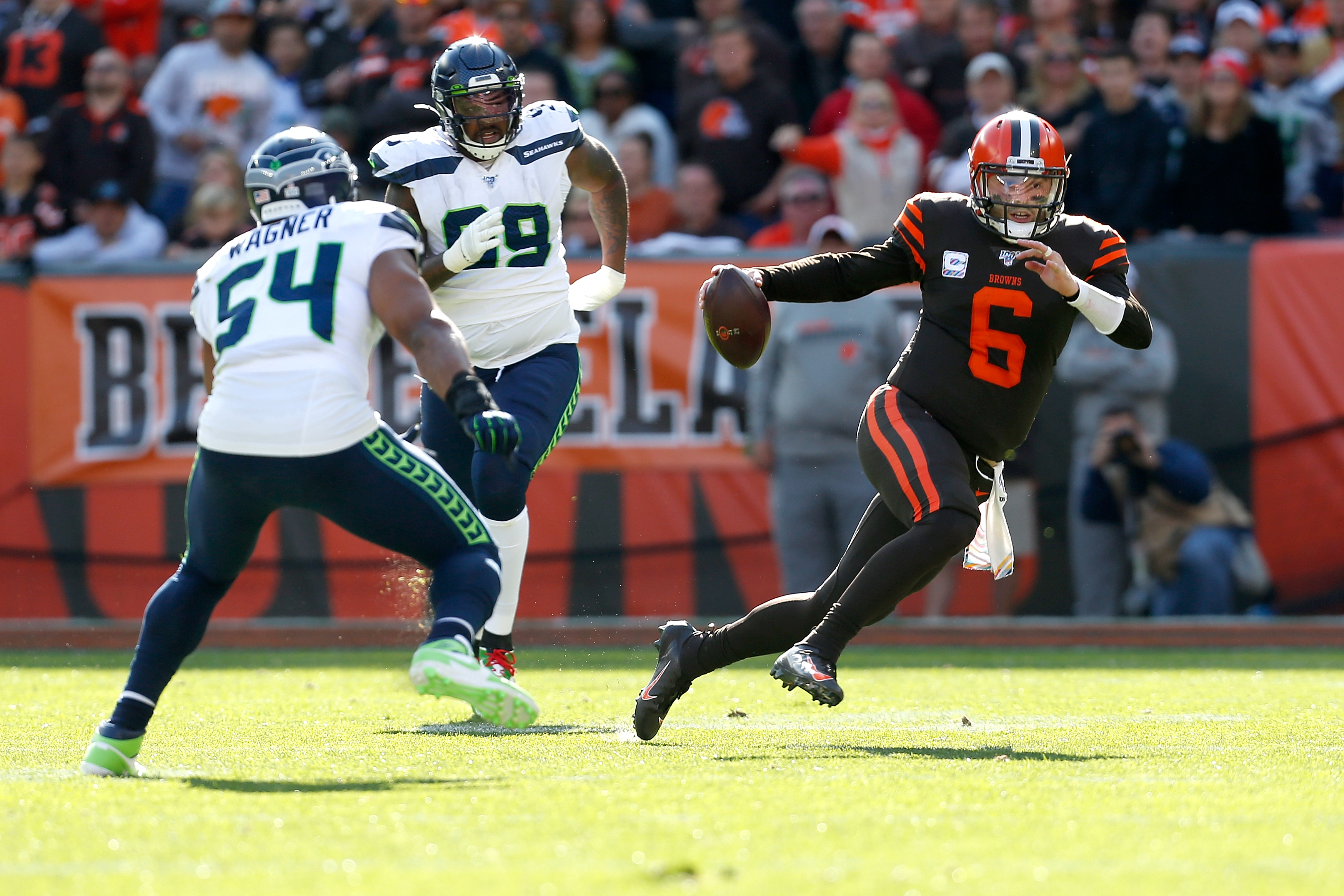 Baker Mayfield of the Cleveland Browns attempts to run the ball past Bobby Wagner of the Seattle Seahawks during the third quarter at FirstEnergy Stadium on October 13, 2019 in Cleveland, Ohio.