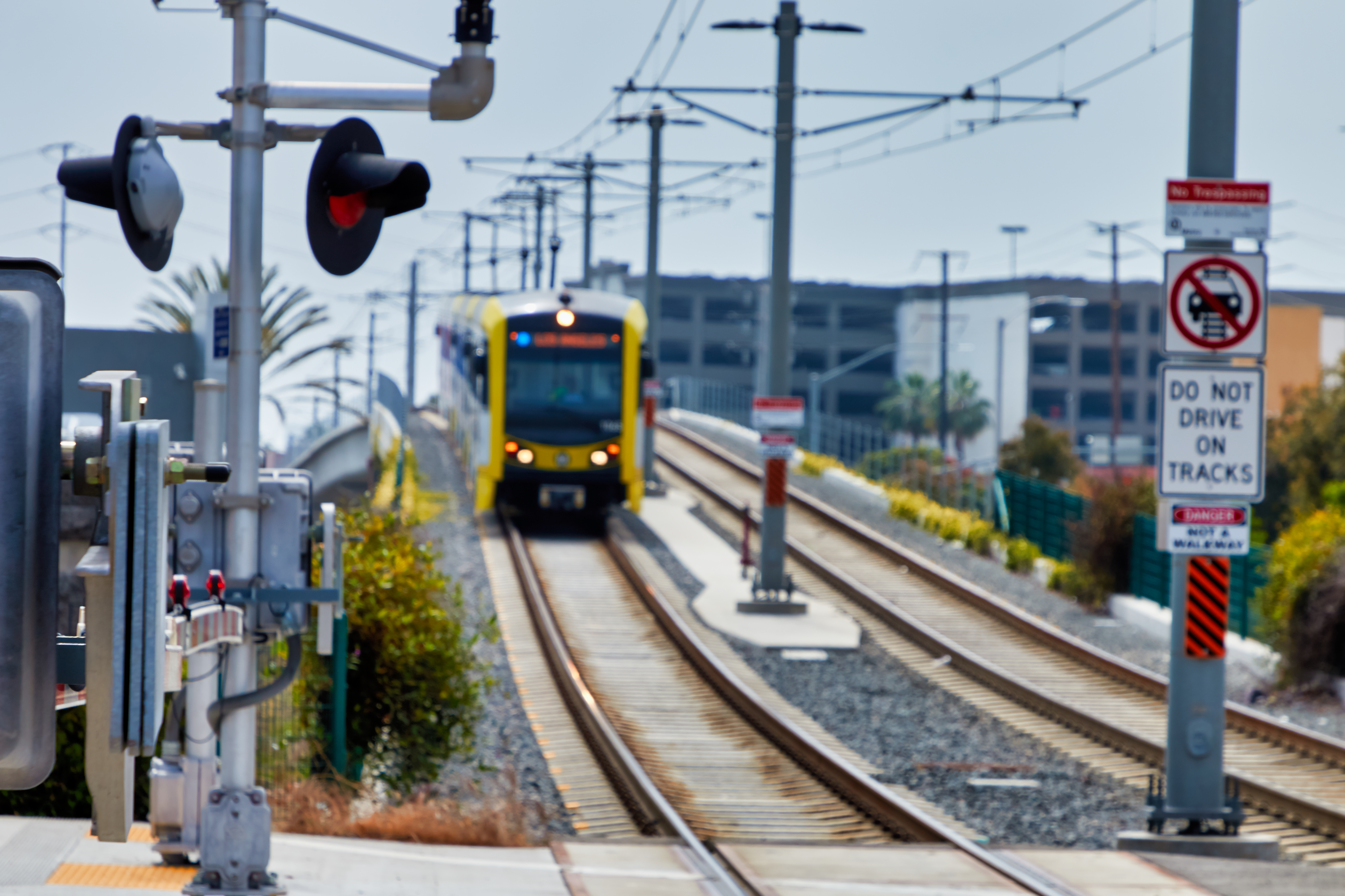 A yellow and black train travels down train tracks and below overheard wires.