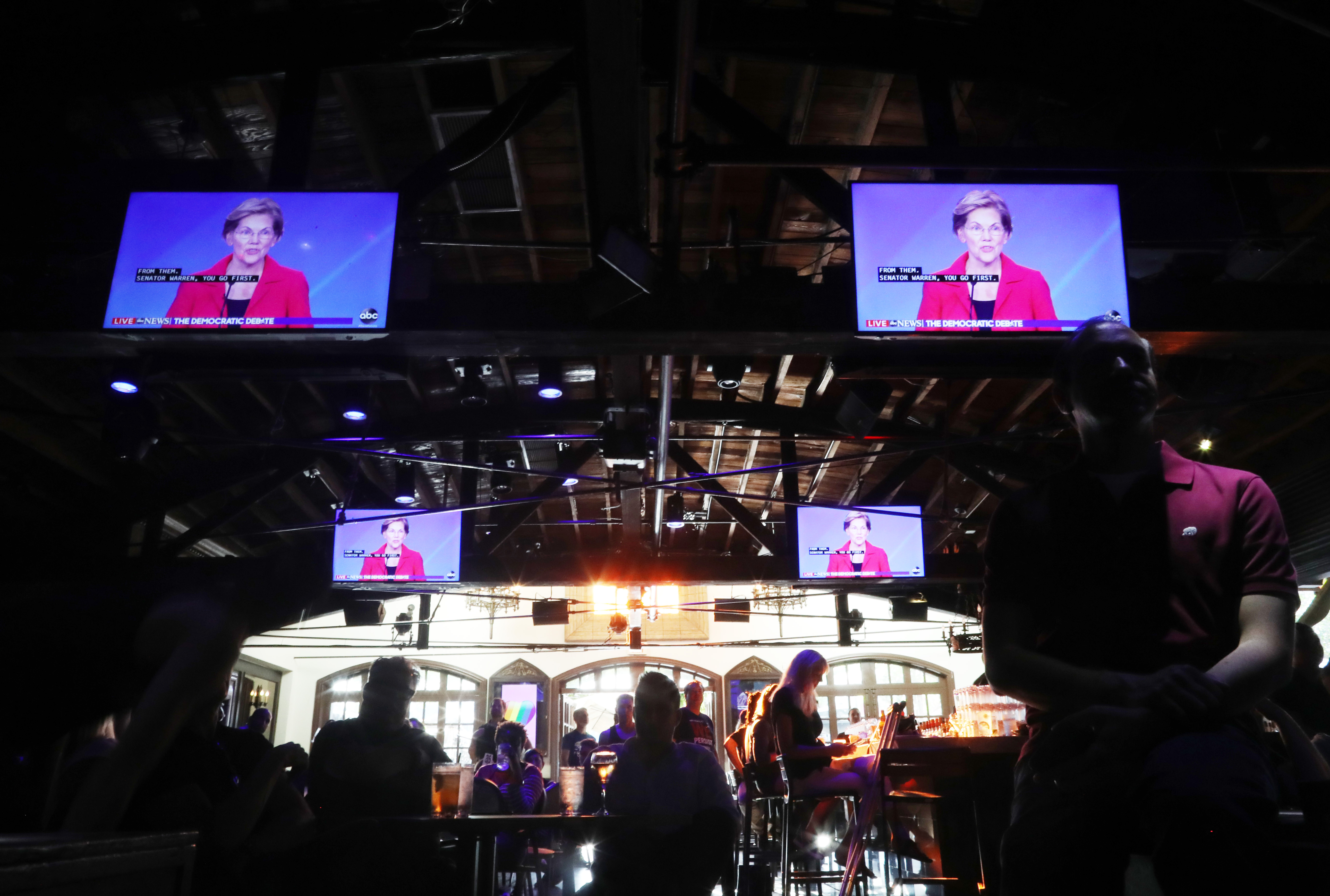 Senator Elizabeth Warren appears on several video screens above a crowd gathered at a bar.