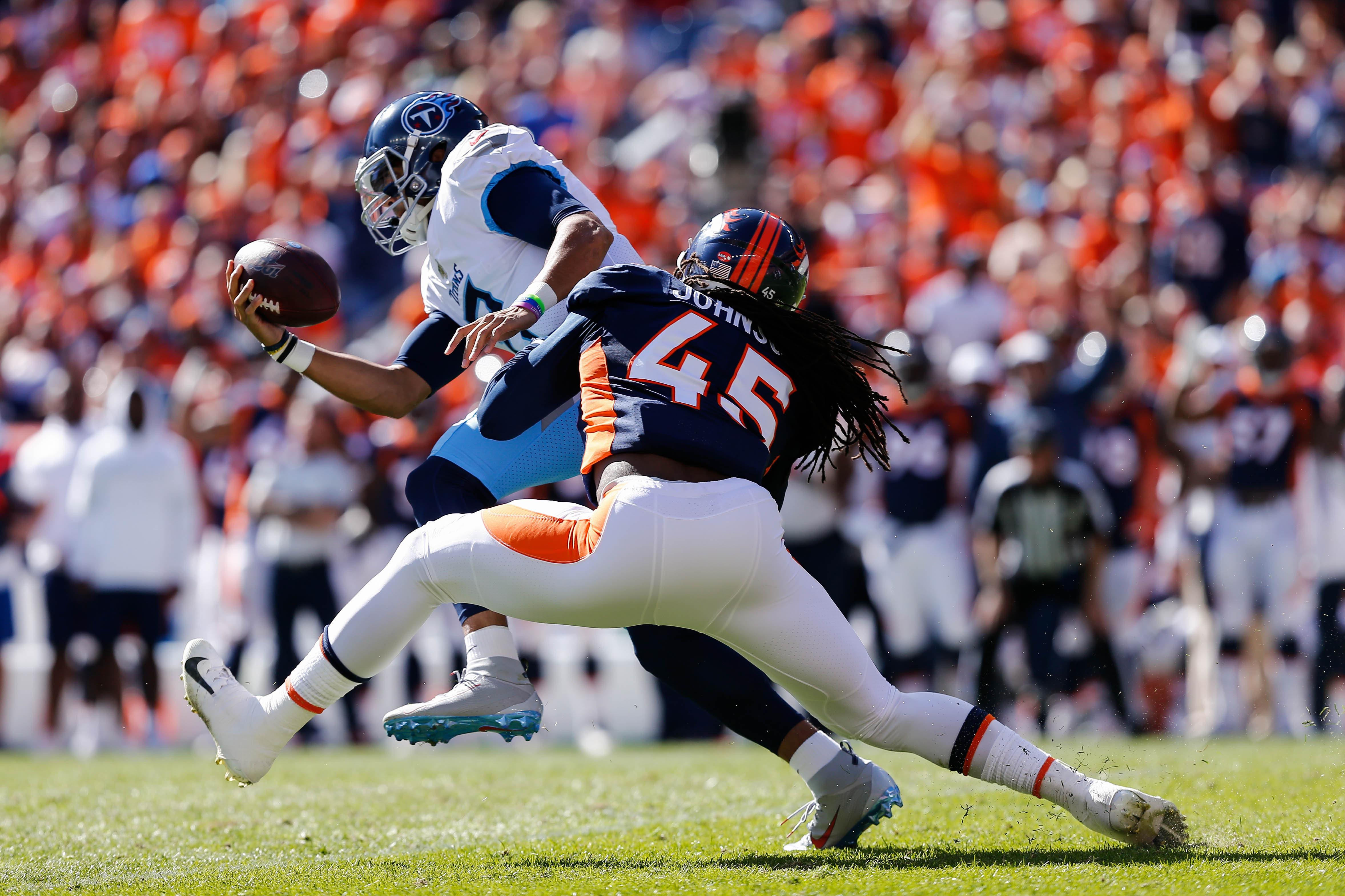 Denver Broncos linebacker Alexander Johnson sacks Tennessee Titans quarterback Marcus Mariota in the first quarter at Empower Field at Mile High.