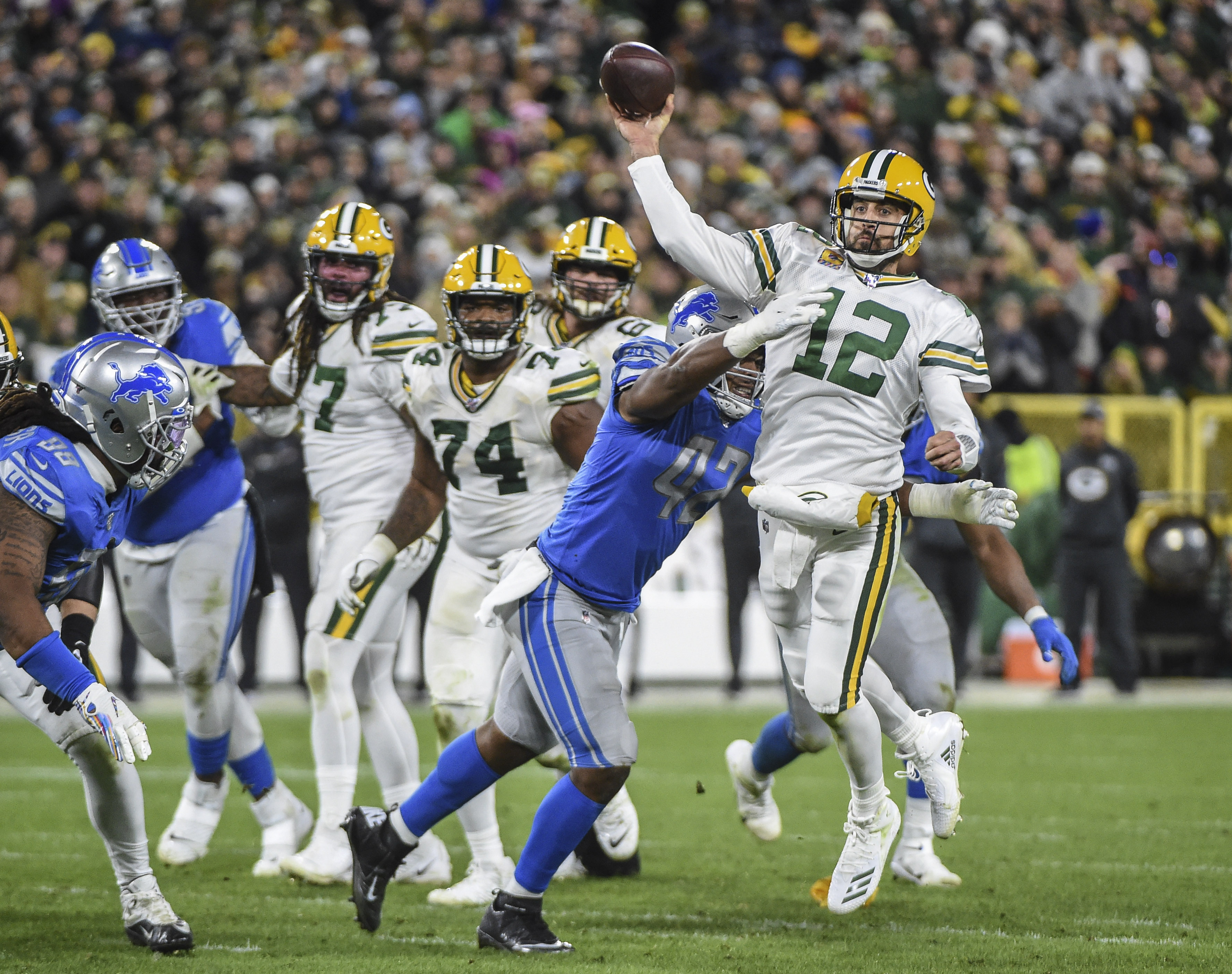Green Bay Packers quarterback Aaron Rodgers throws a pass while under pressure from Detroit Lions linebacker Devon Kennard in the fourth quarter at Lambeau Field.
