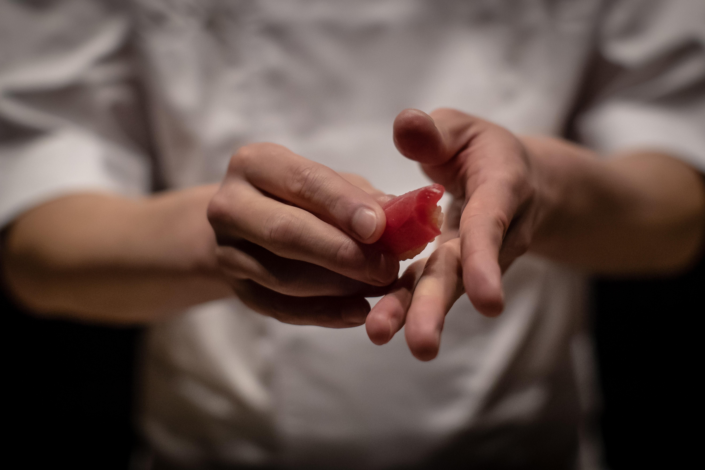 Chef Shigeyuki Tsunoda, in a close-up shot showing only his hands, prepares crimson lean tuna nigiri sushi