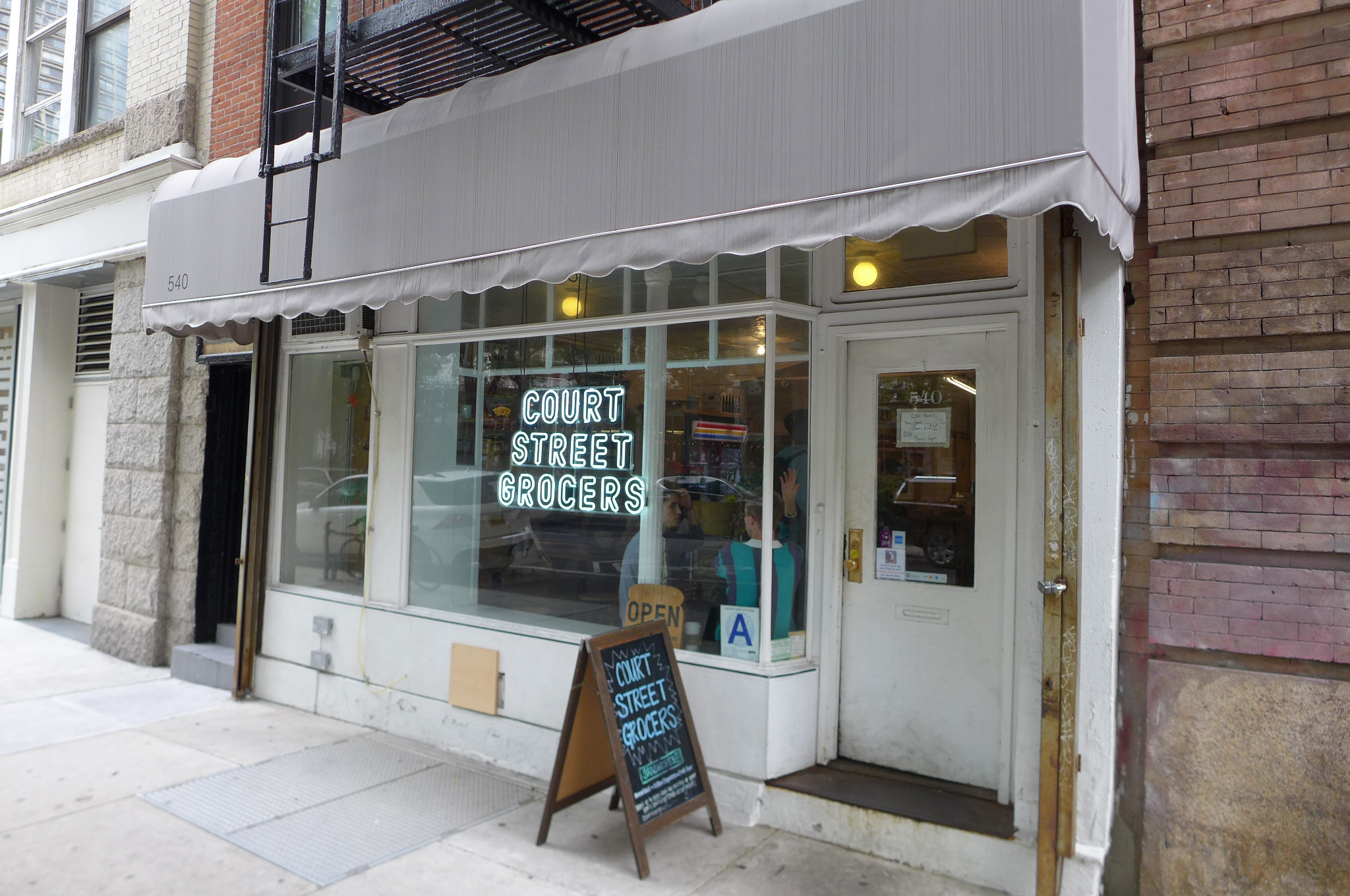 The storefront of Court Street Grocers, seen from an oblique angle, has a white neon sign burning in the window...