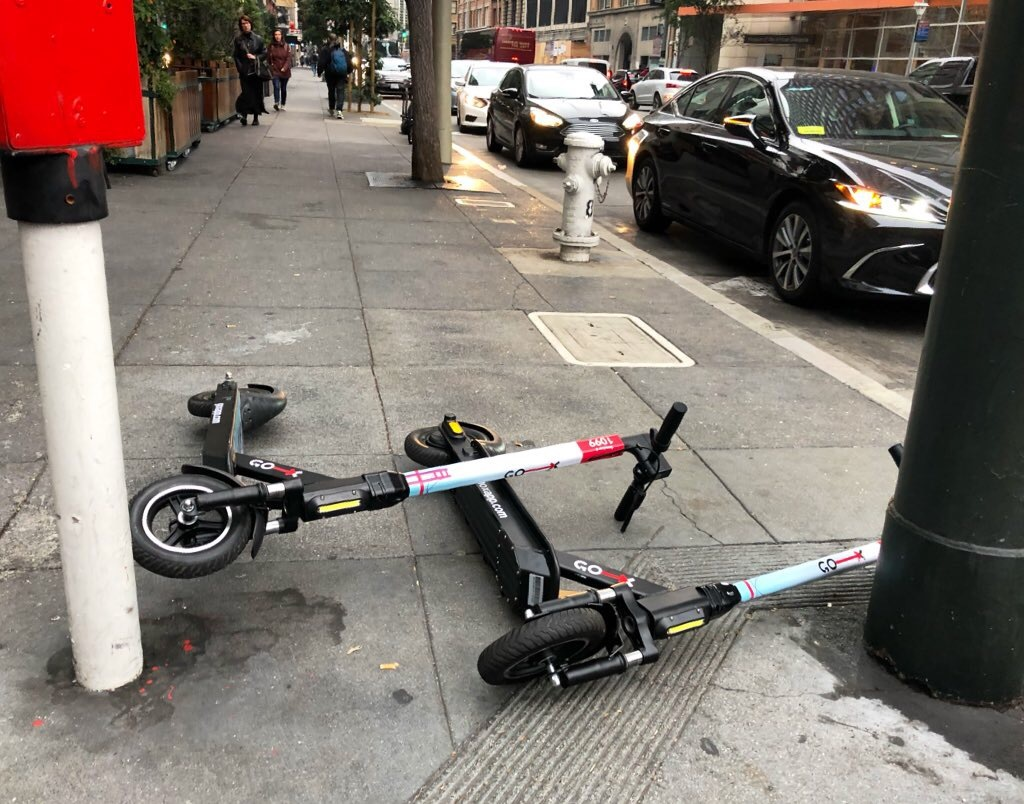 Two e-scooters lying on the sidewalk.