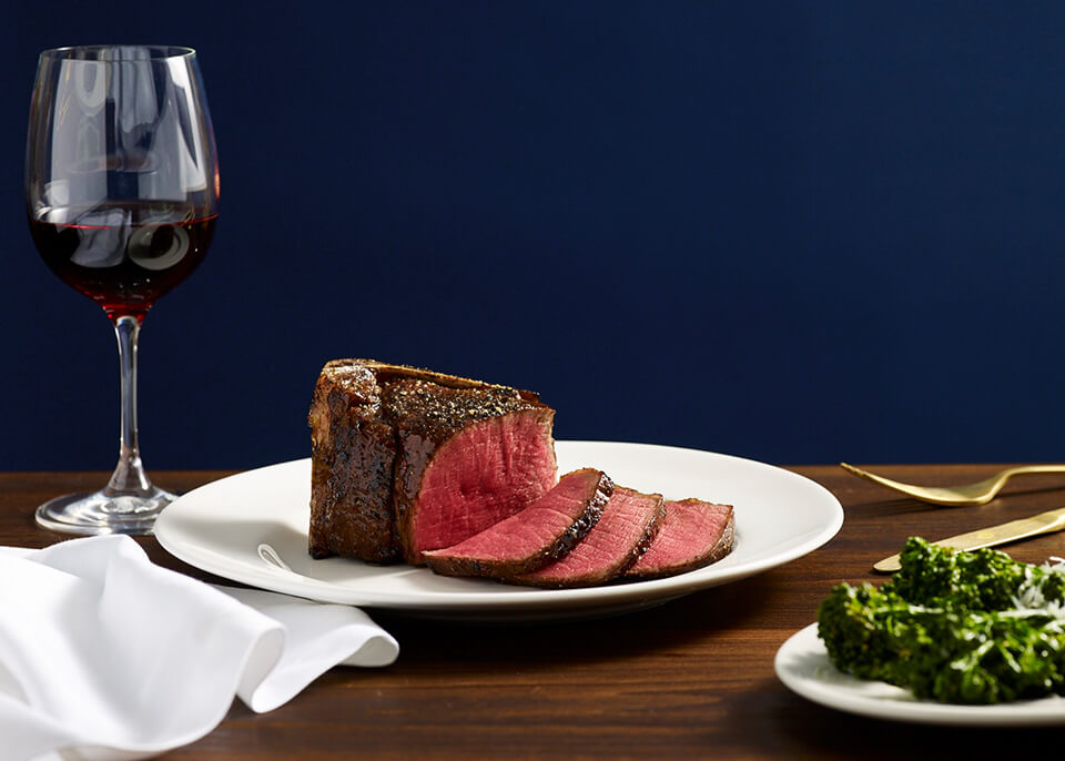 An austere plating of filet mignon accompanied by a glass of red wine and some bitter greens. It all sits atop a dark wooden table, and is backdropped by a navy blue wall.