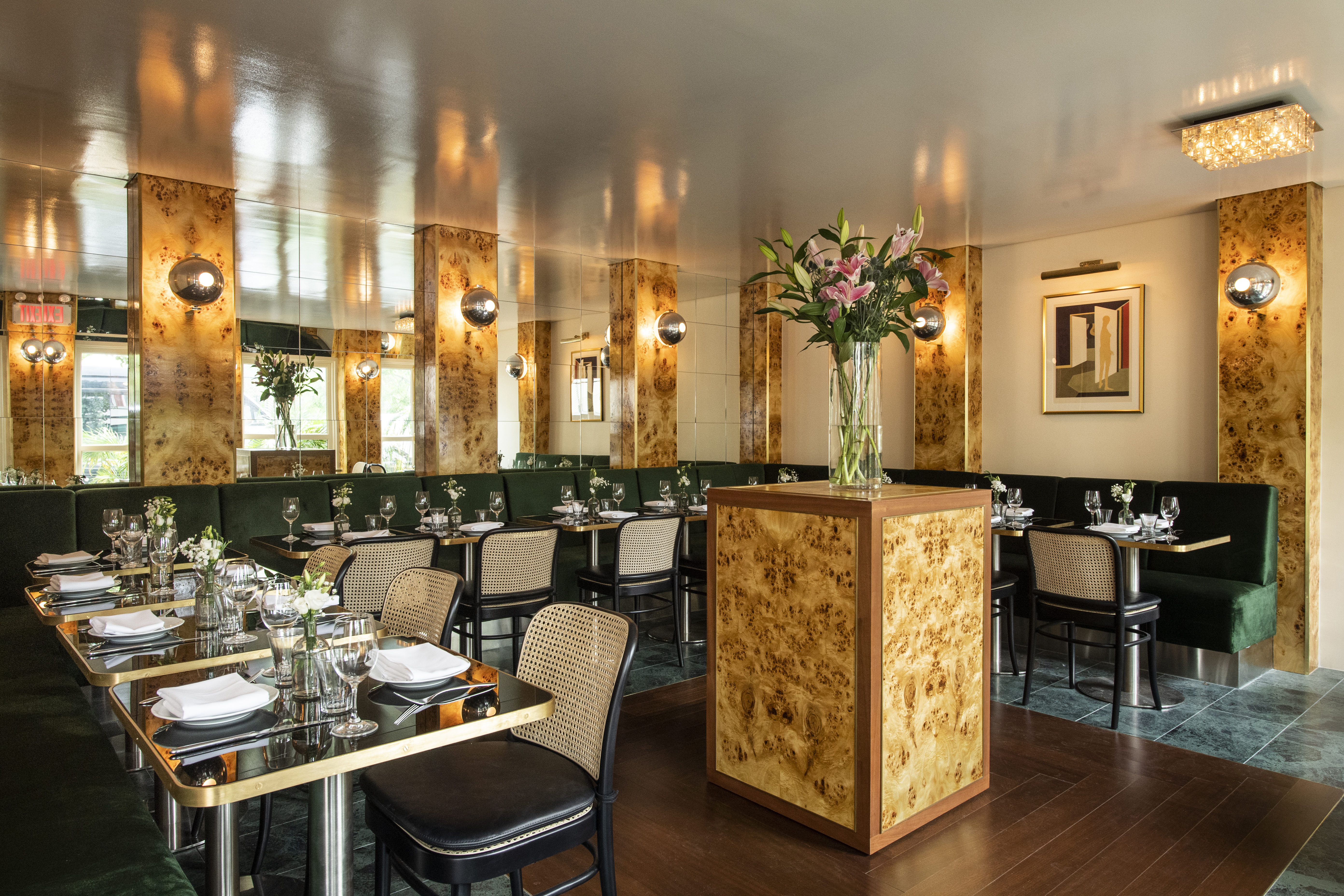 The golden dining rom of Babs, with green banquettes lining the sides