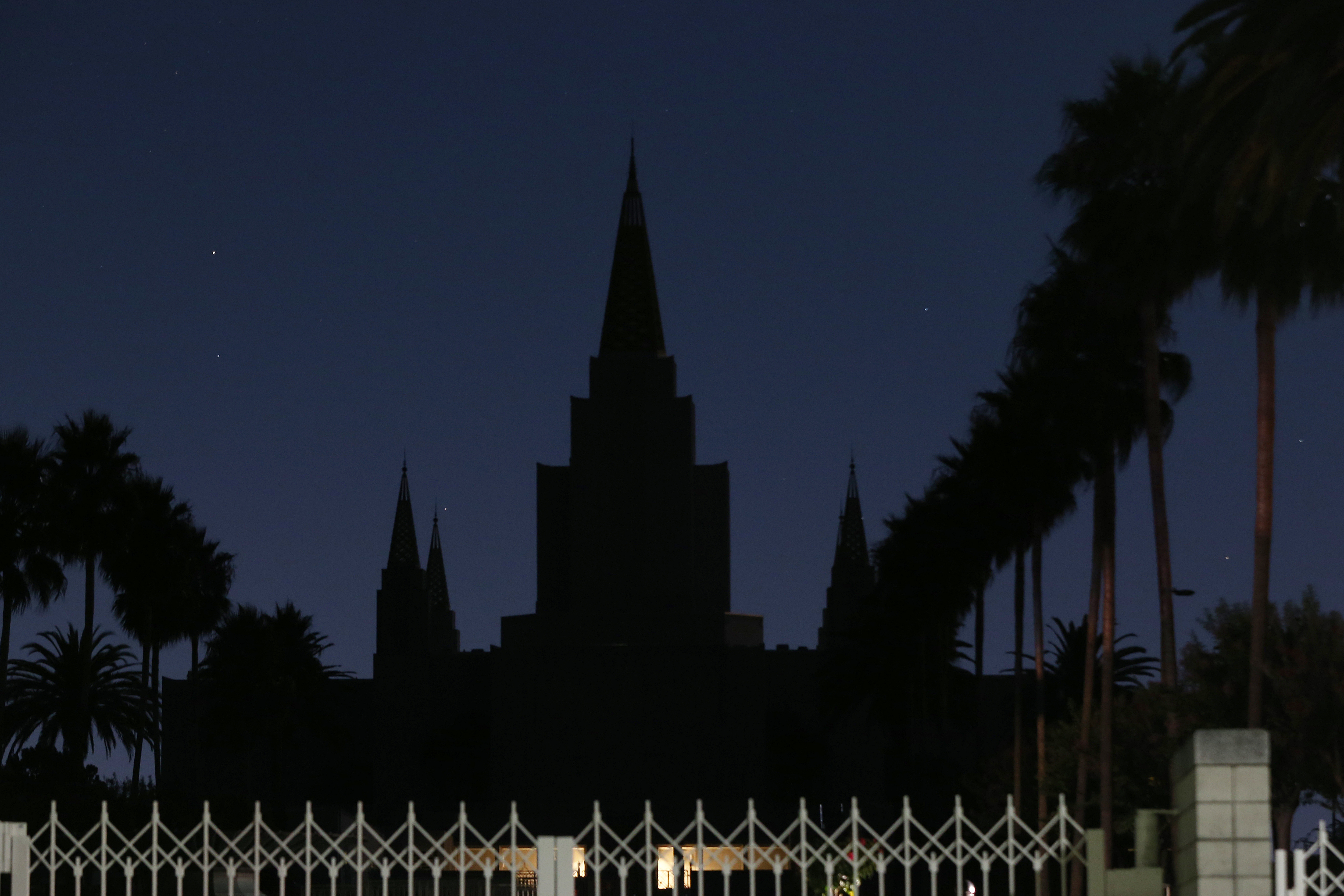 The dark silhouette of an Oakland building with tall spires, set against a twilight sky.