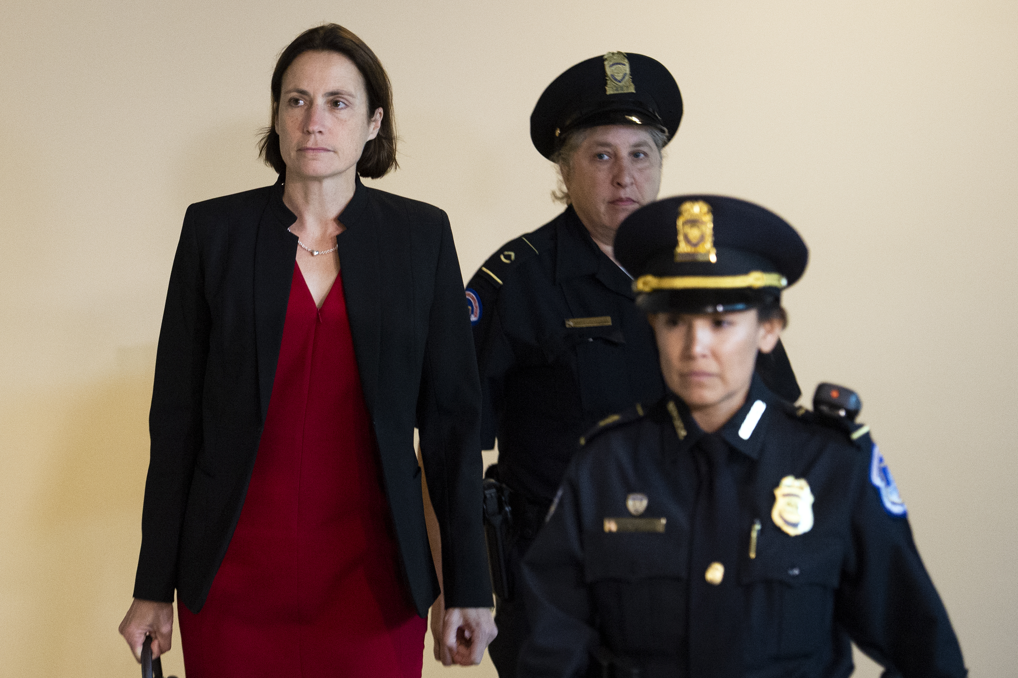 Hill walks down Capitol Hill's hallways alongside police officers.
