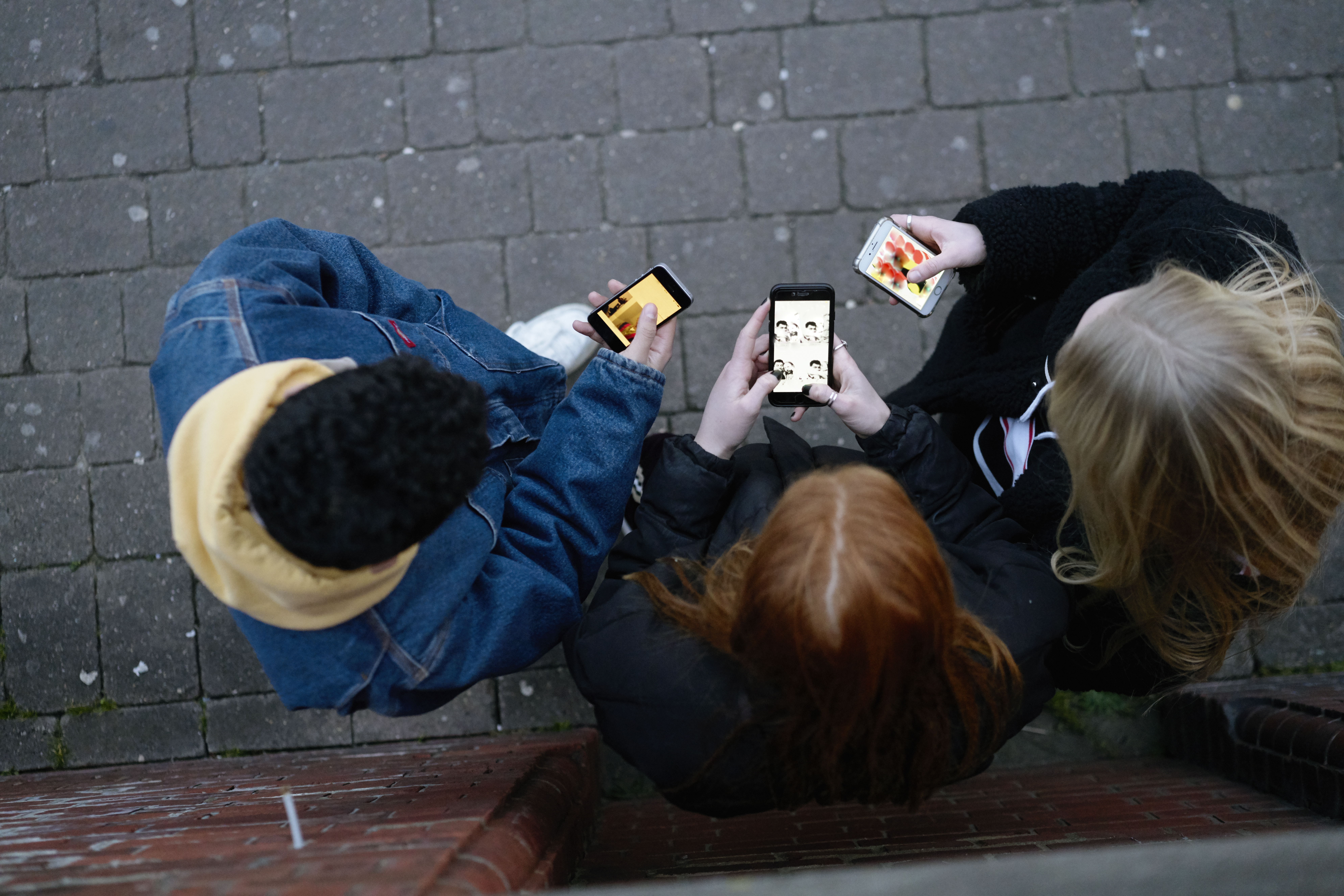 A group of three teenagers standing on a city sidewalk, seen from above, are looking at their smartphones.