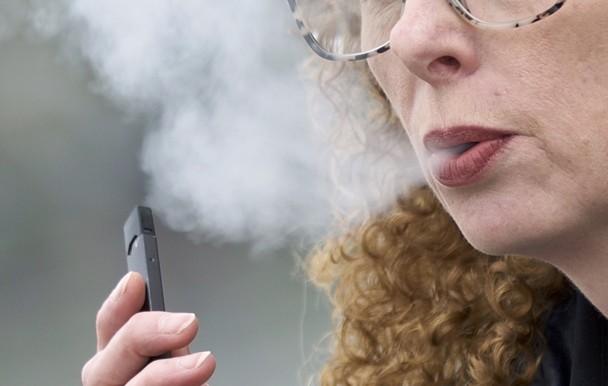 In this April 16, 2019 file photo, a woman exhales while vaping from a Juul pen e-cigarette in Vancouver, Wash.